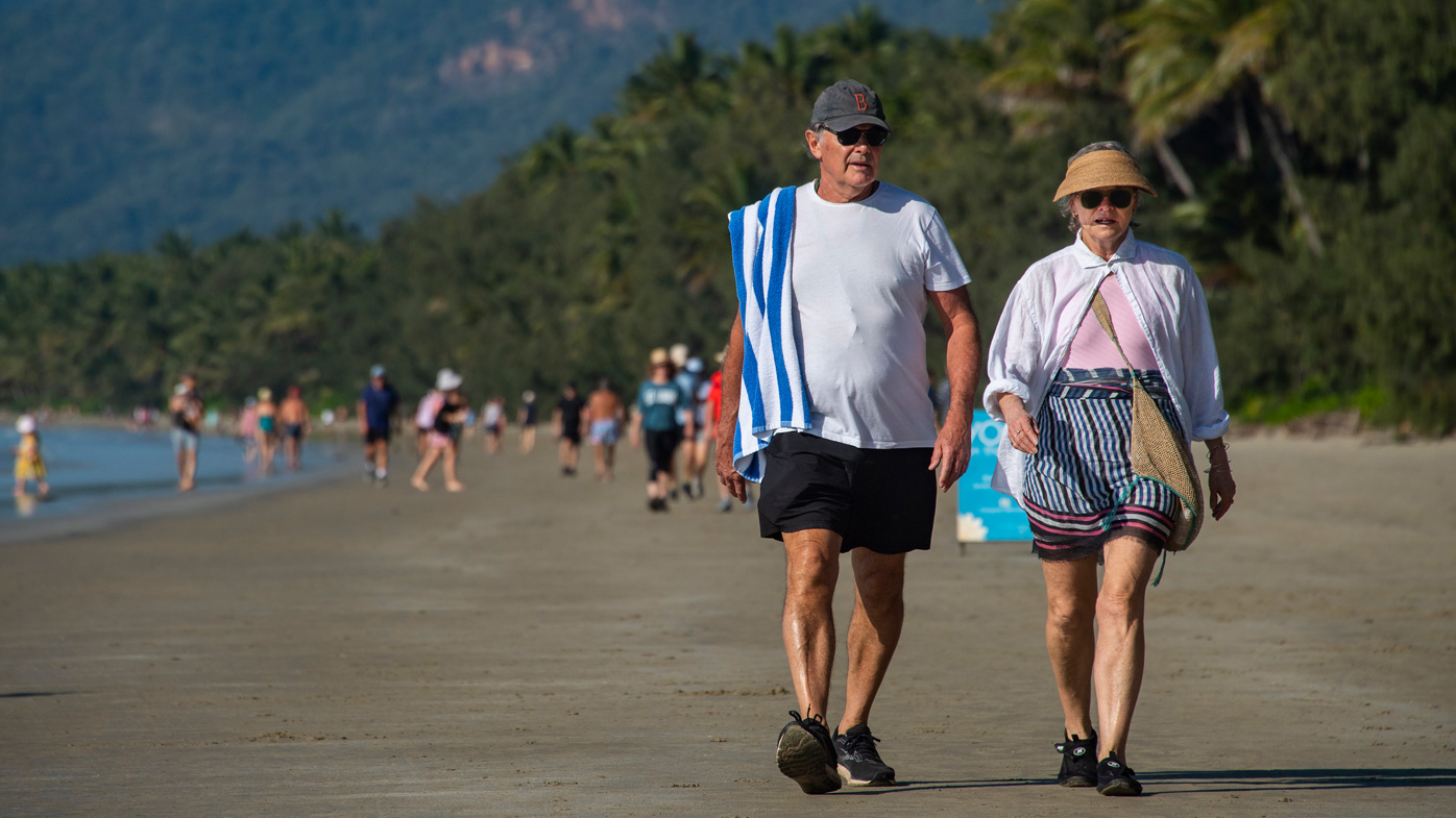 People walk along on a beach on North Queensland, as Cairns faces a COVID-19 scare and snap three-day lockdown.
