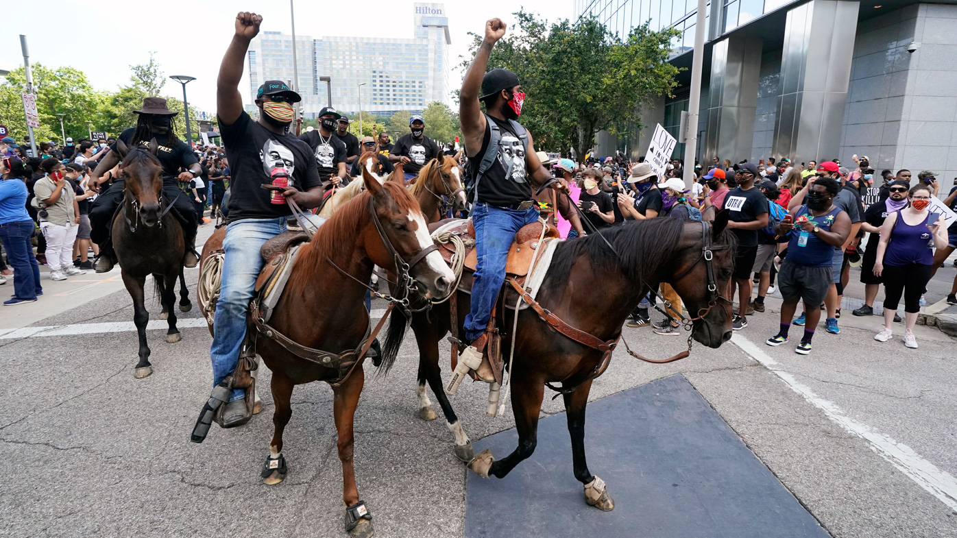 People march and ride horses to protest the death of George Floyd in Houston. Floyd died after a Minneapolis police officer pressed his knee into Floyd's neck for several minutes even after he stopped moving and pleading for air.