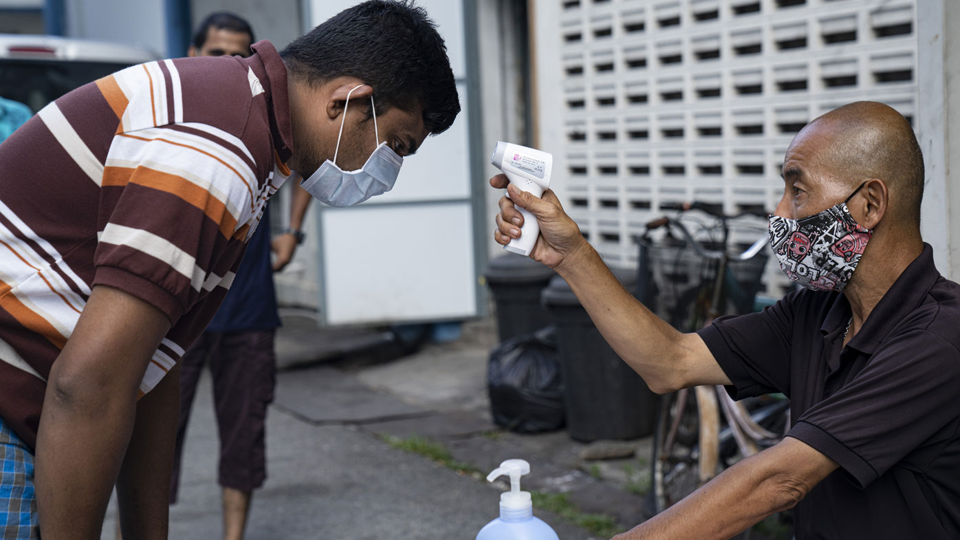 A migrant worker wearing protective face mask has his temperature checked by a security guard before leaving a factory-converted dormitory.