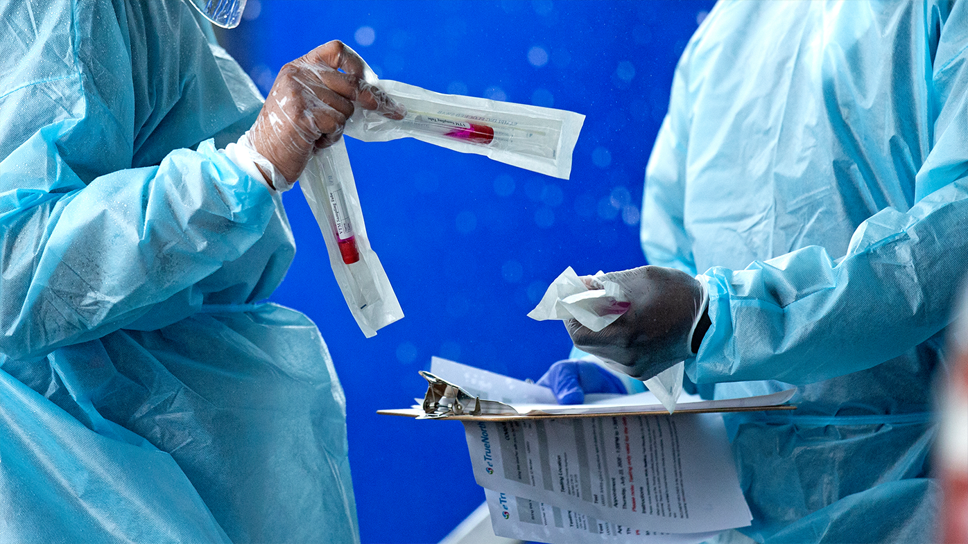 FILE - In this July 23, 2020, file photo, health care workers prepare a COVID-19 test sample before a person self-administered a test at the COVID-19 drive-thru testing center at Miami-Dade County Auditorium in Miami. (David Santiago/Miami Herald via AP)