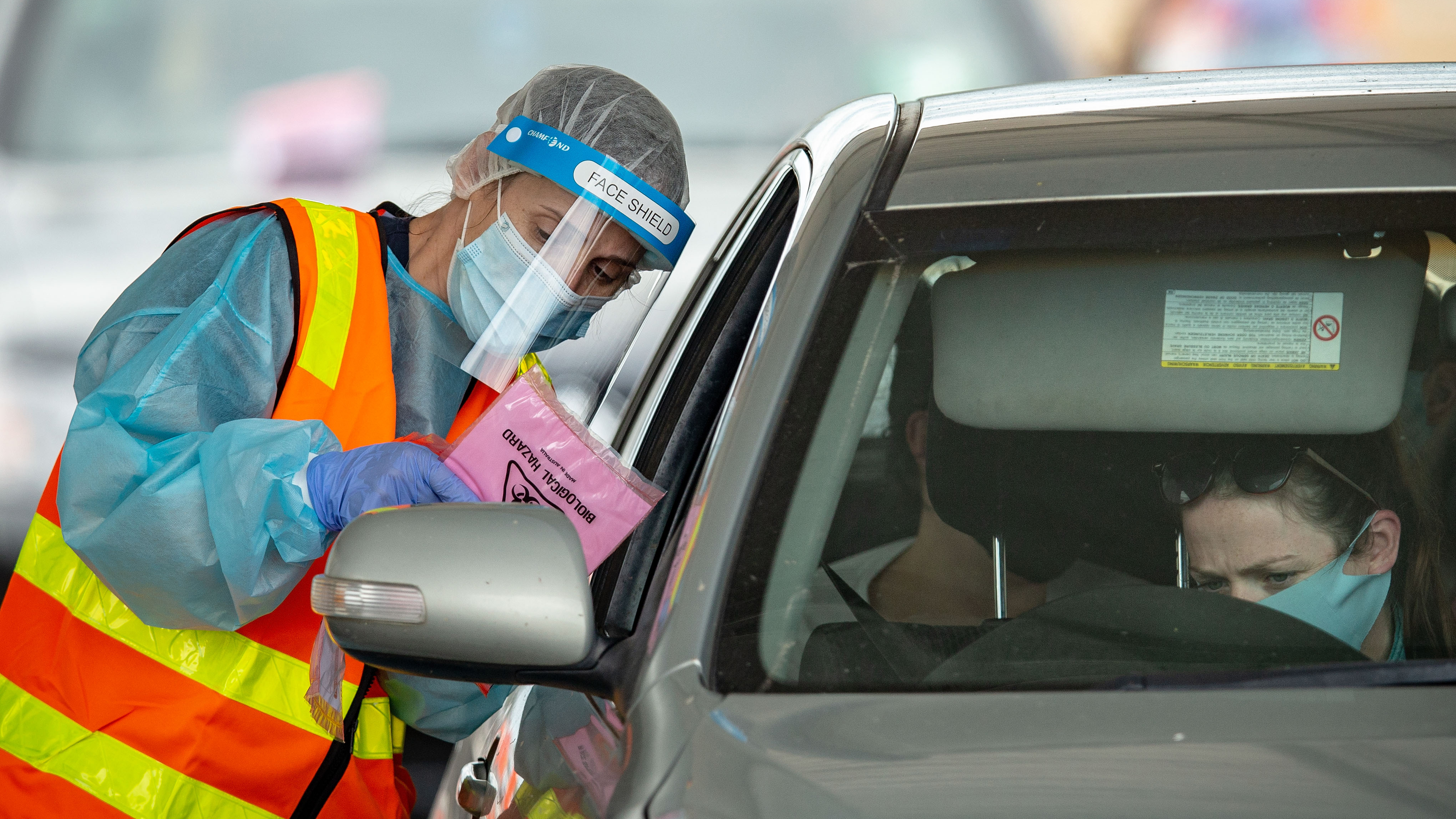Medical professionals conduct COVID-19 tests at a drive through testing clinic in the Shepparton Sports Precinct in Shepparton, Victoria.