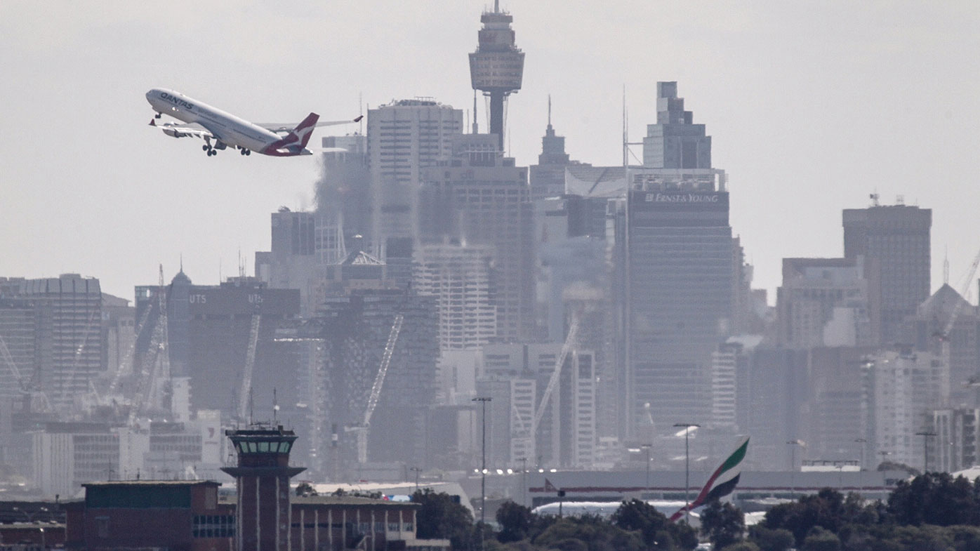 Qantas commercial aircraft taking off across Sydney's skyline photographed From Dolls Point on Botany Bay