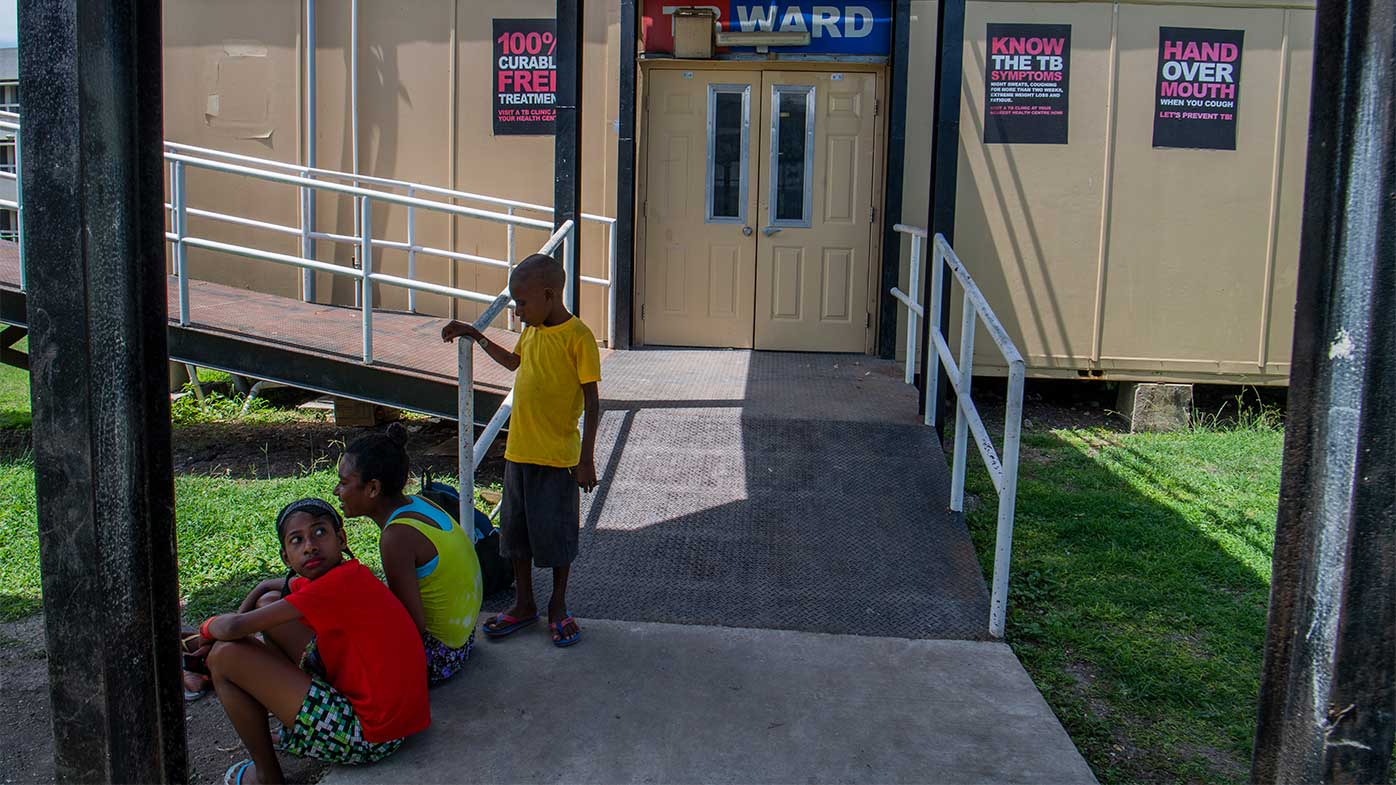 Children sit outside a ward of Port Moresby General Hospital.