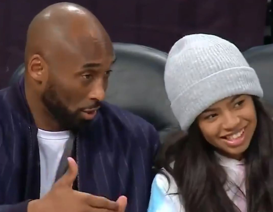 Kobe Bryant gives daughter Gianna some courtside tips at a game in December.