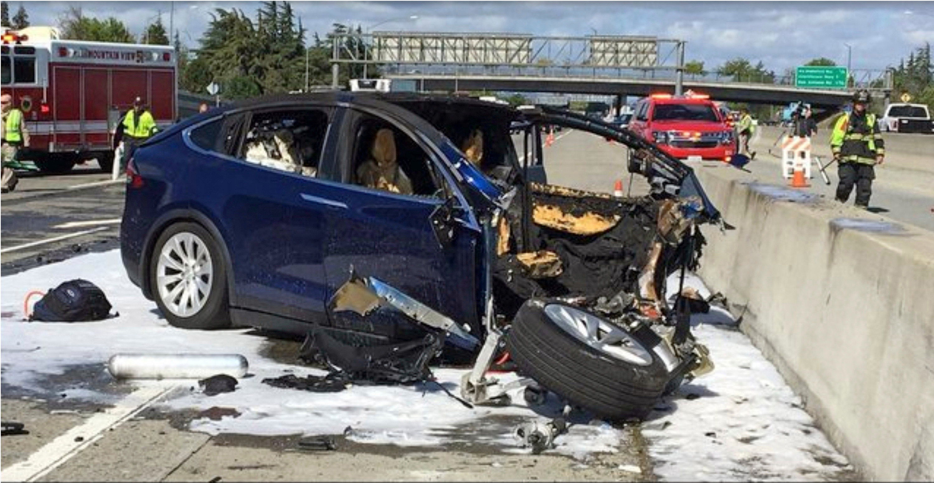 Emergency personnel work a the scene where a Tesla electric SUV crashed into a barrier on U.S. Highway 101 in California.