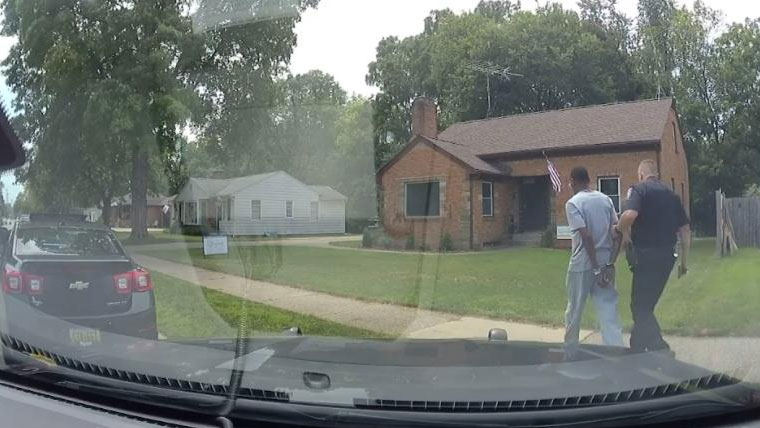 Real estate agent Eric Brown is seen with a Wyoming, Michigan, police officer on August 1, 2021, after he was handcuffed while giving a tour of a home for sale to a Black father and his son.
