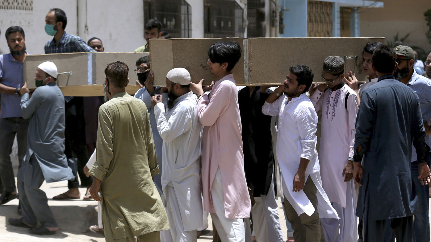 People carry the casket of the victims of Friday's plane crash for funeral prayers in Karachi, Pakistan, Saturday, May 23, 2020