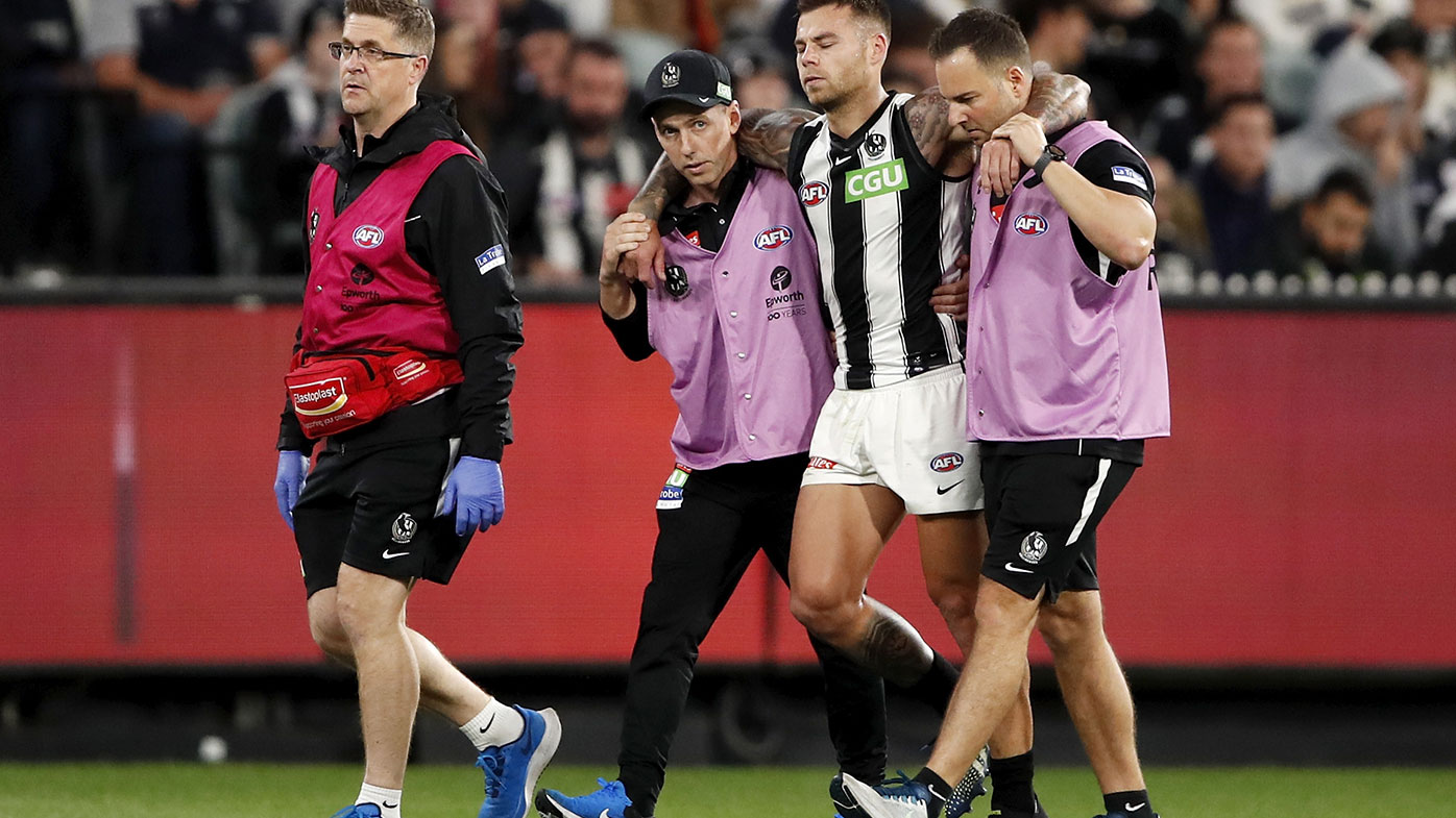 Jamie Elliott is helped from the field during Collingwood's Round Two win over Carlton at the MCG.