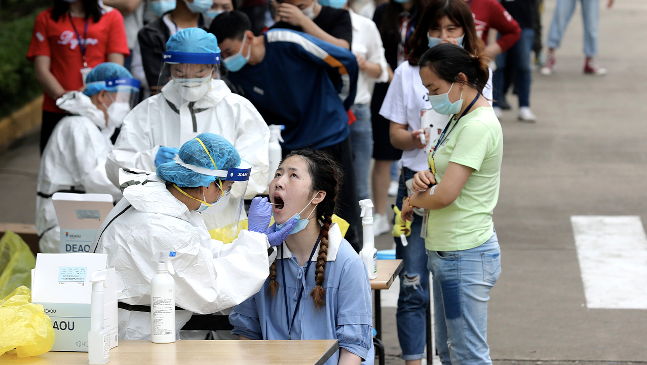 Employees line up for medical workers to take swabs for the coronavirus test at a large factory in Wuhan in central China's Hubei province Friday, May. 15, 2020. Wuhan have begun testing inhabitants for the coronavirus as a program to test everyone in the Chinese city of 11 million people in 10 days got underway.  (Chinatopix Via AP) CHINA OUT