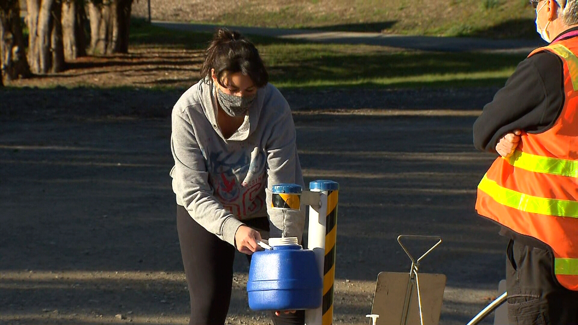 A woman fills up a water bottle because of contamination fears.