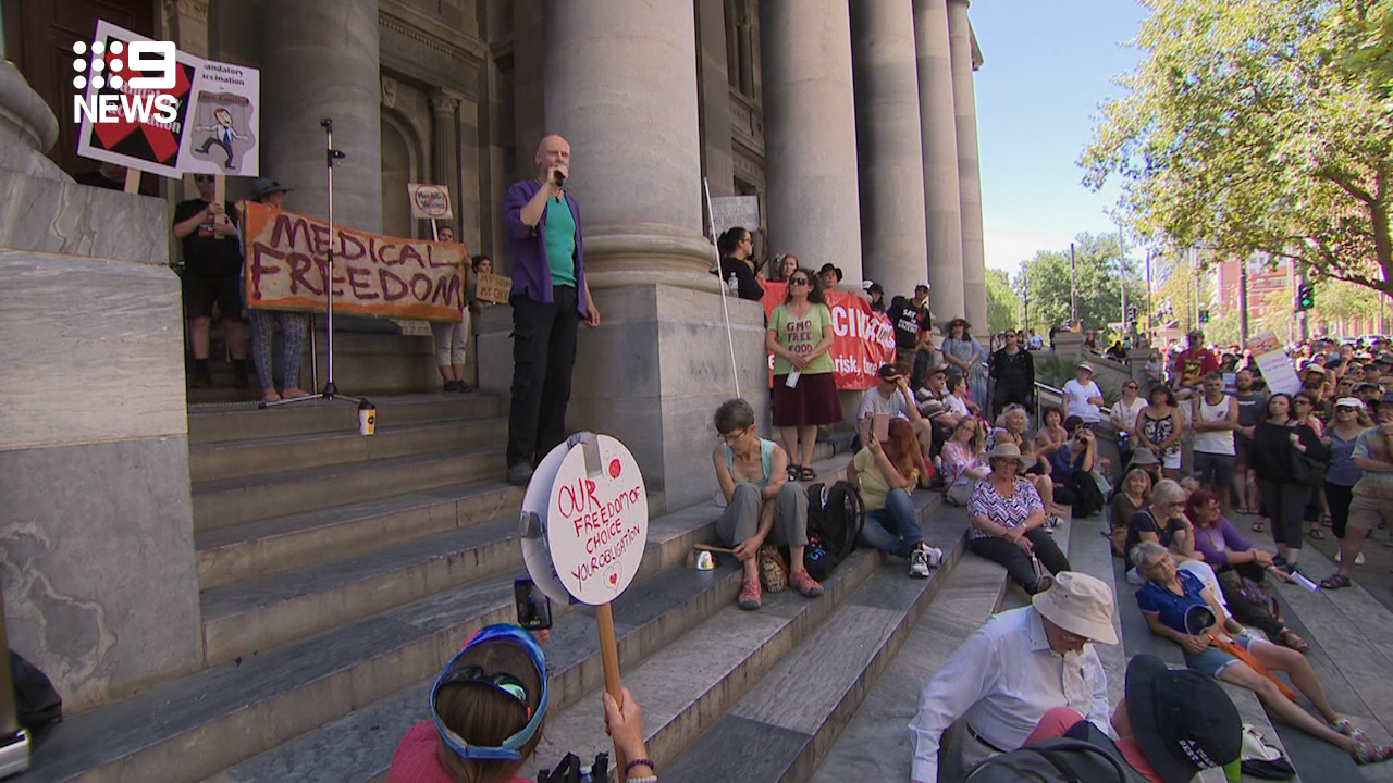 People gather with signs and listen to speeches in Adelaide today.