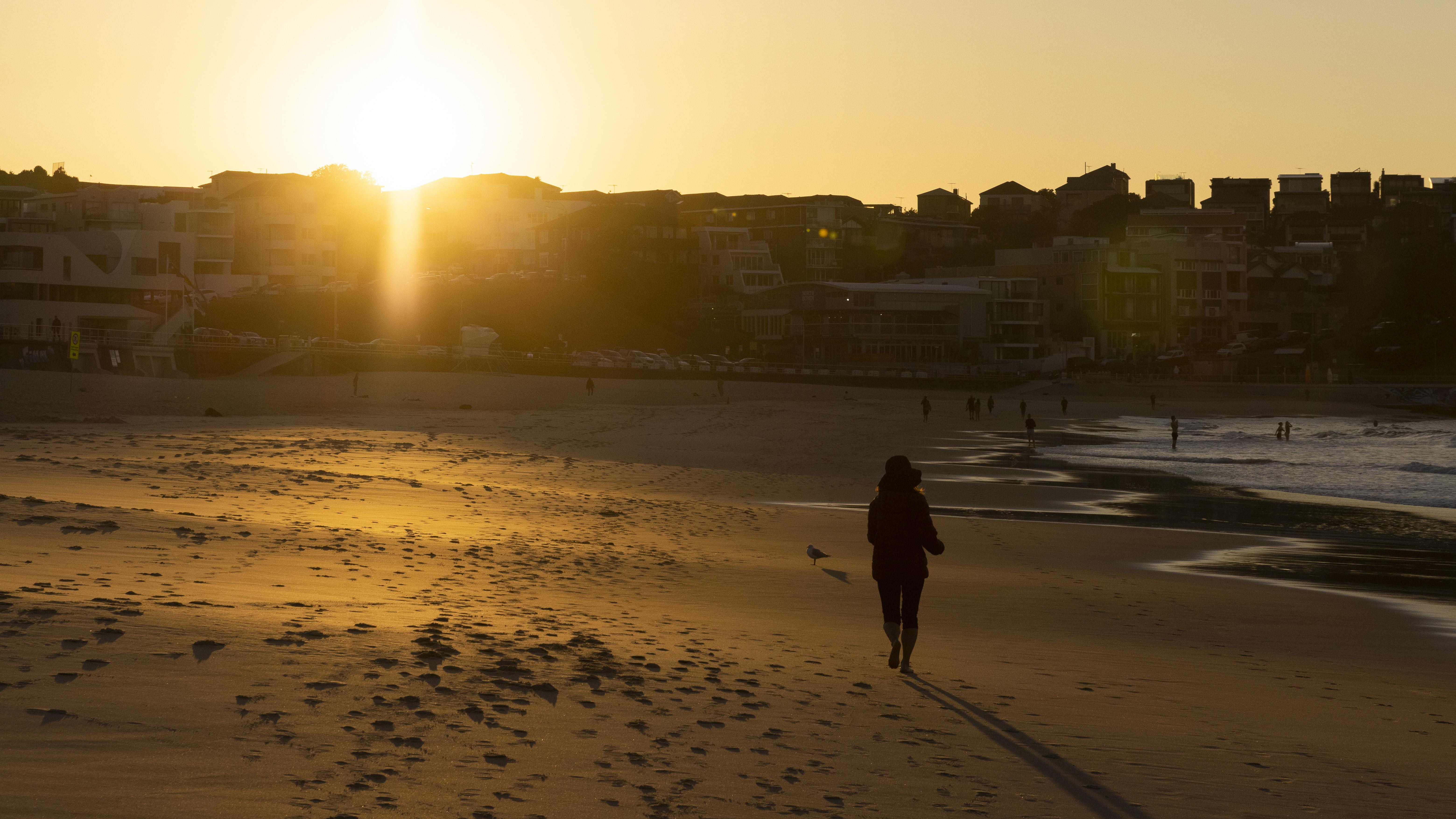A runner at sunrise on Bondi Beach in Sydney.