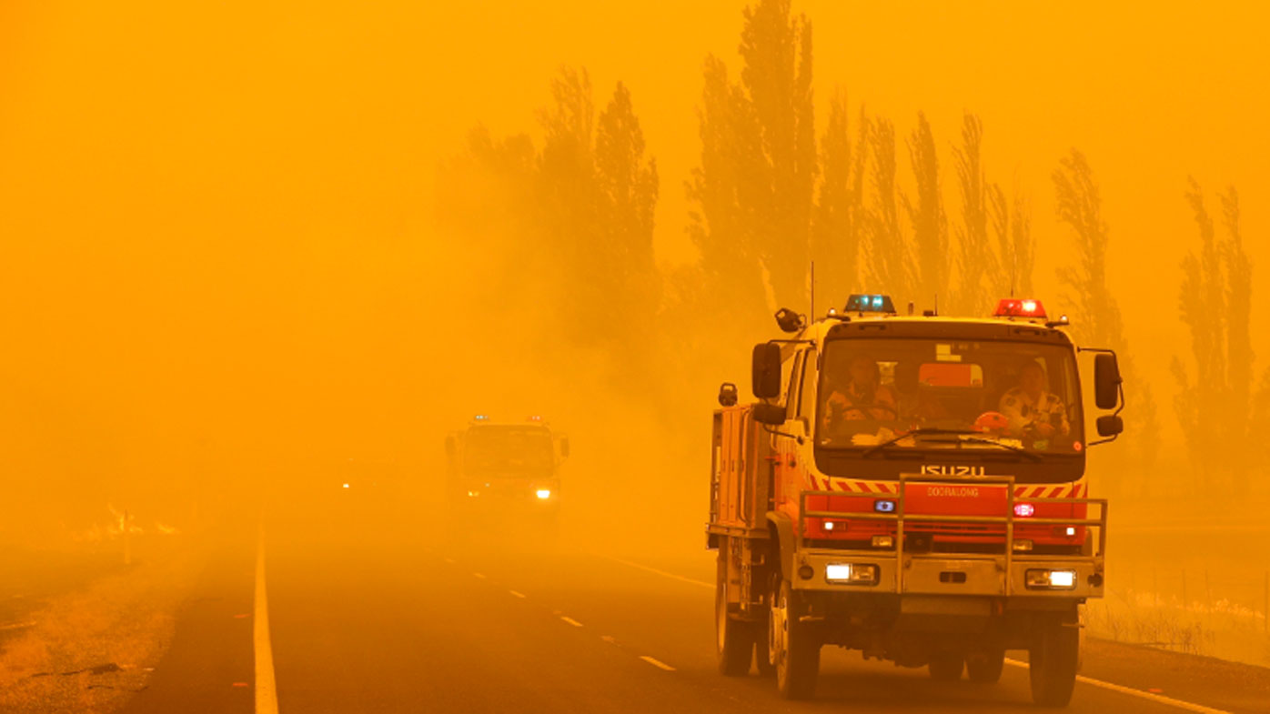 Fire burns in the grass along the road as firetrucks pass by near Bumbalong, south of the Australian capital, Canberra