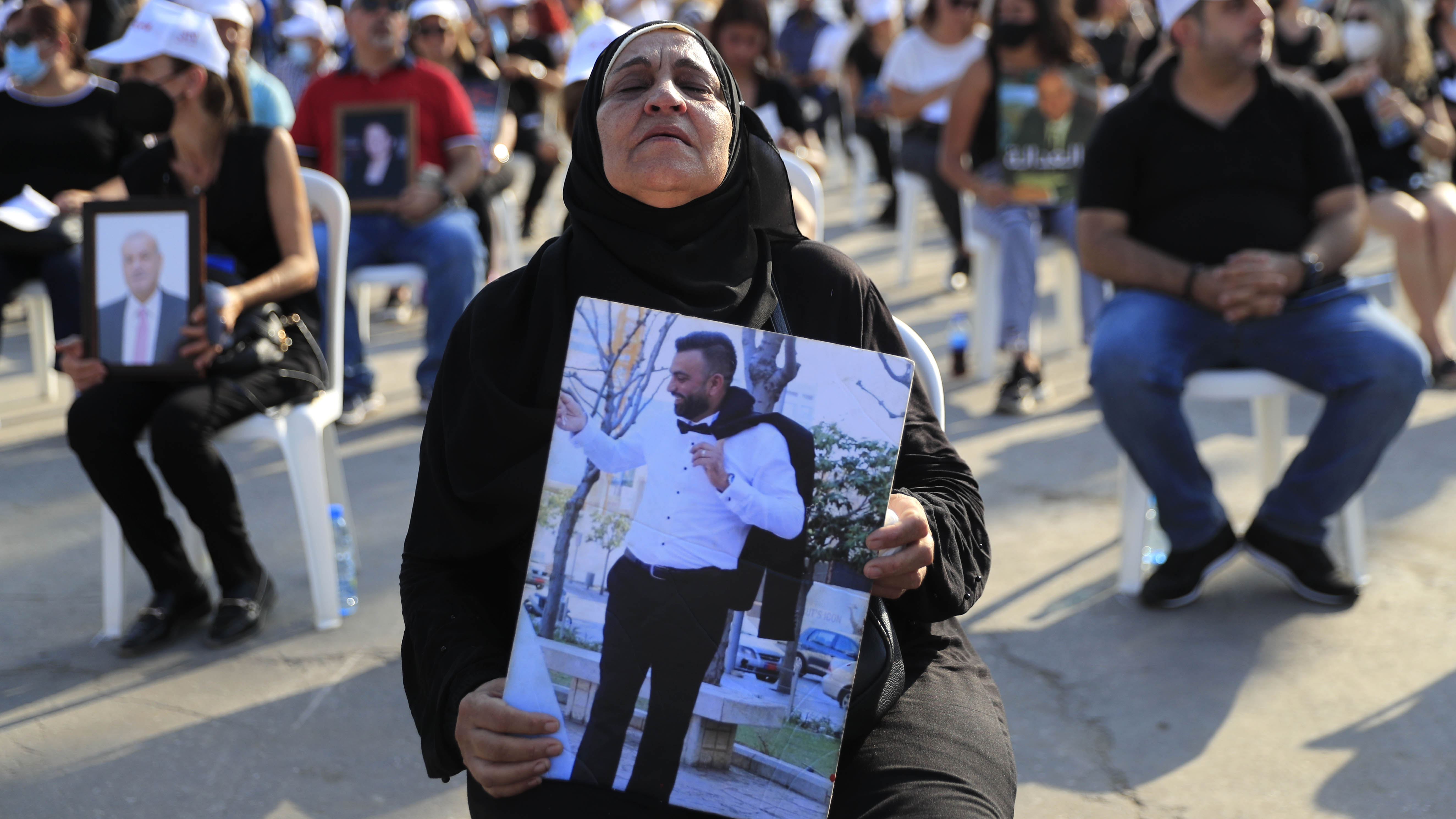 The mother of a victim who was killed in the massive blast last year at the Beirut port holds a portrait of her son as she attends a Mass held to commemorate the first year anniversary.