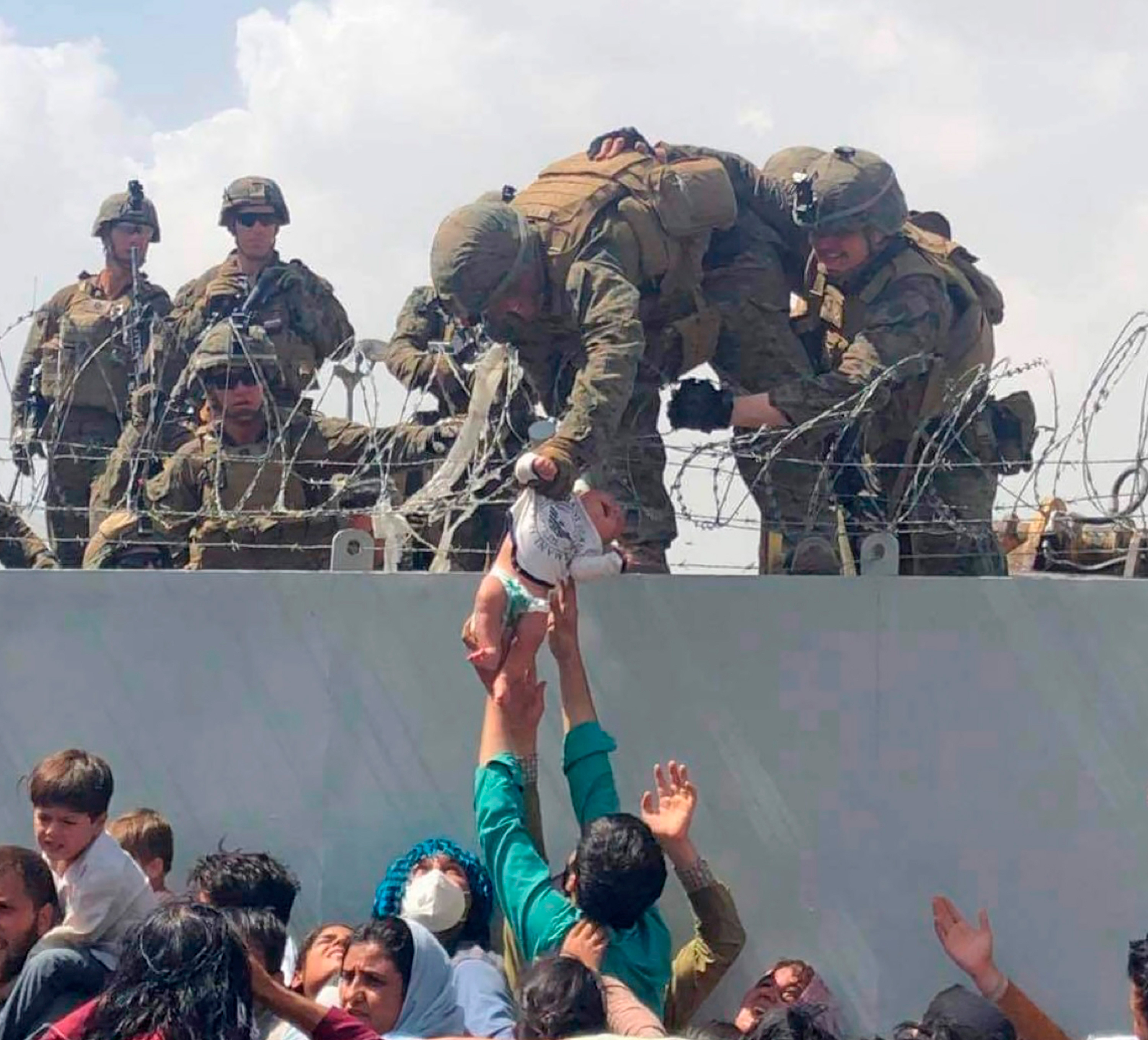 A baby being lifted across a wall at Kabul Airport in Afghanistan by US soldiers, during chaotic scenes last week.
