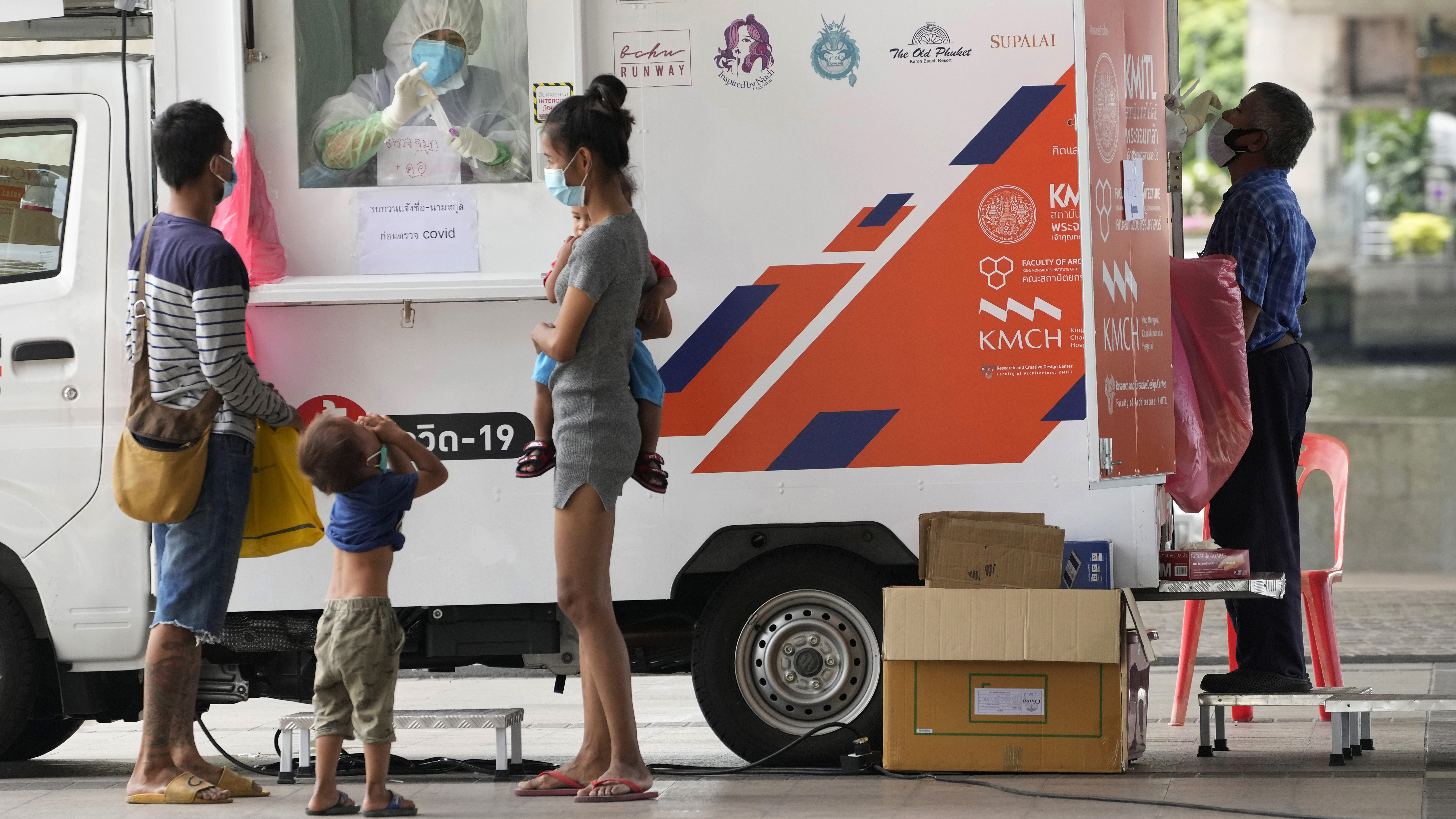 Health workers collect nasal swabs from locals for coronavirus testing at a mobile facility in Bangkok, Thailand.