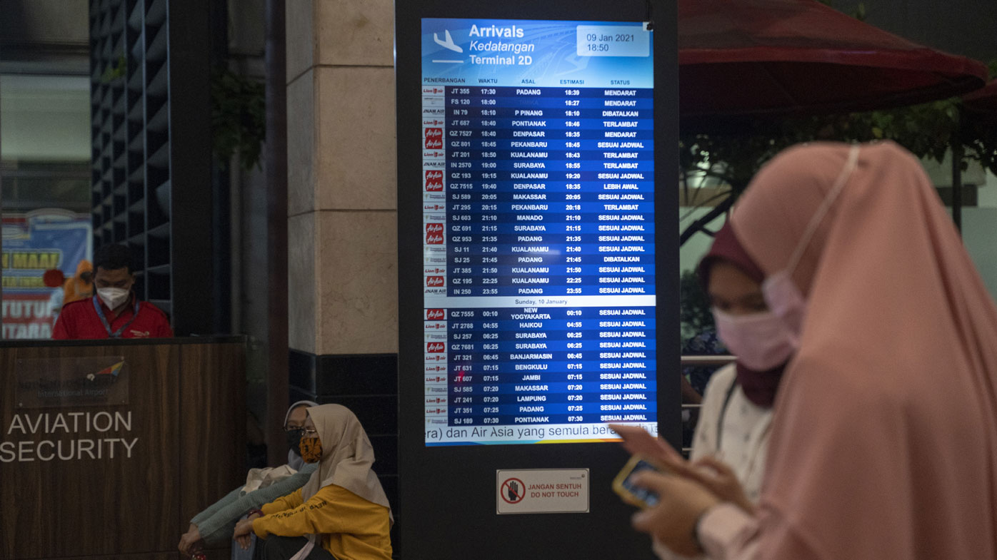 People watch a schedule board at the Crisis centre in Soekarno Hatta Airport, on January 09, 2021 in Jakarta, Indonesia