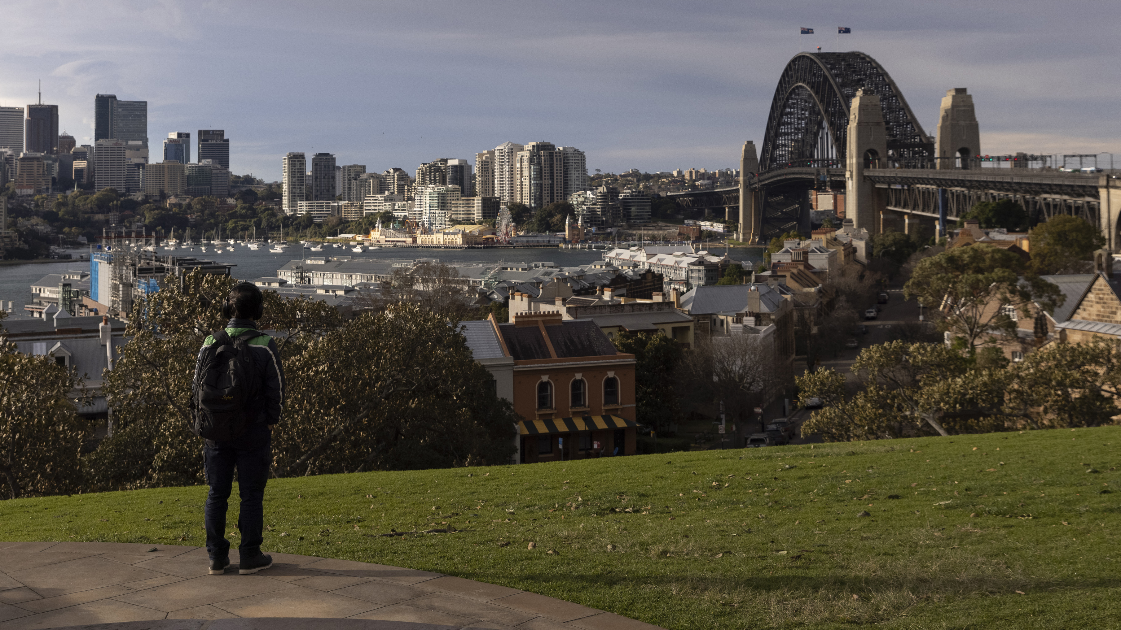 A person looks out over the Harbour Bridge from Observatory Hill in Sydney.