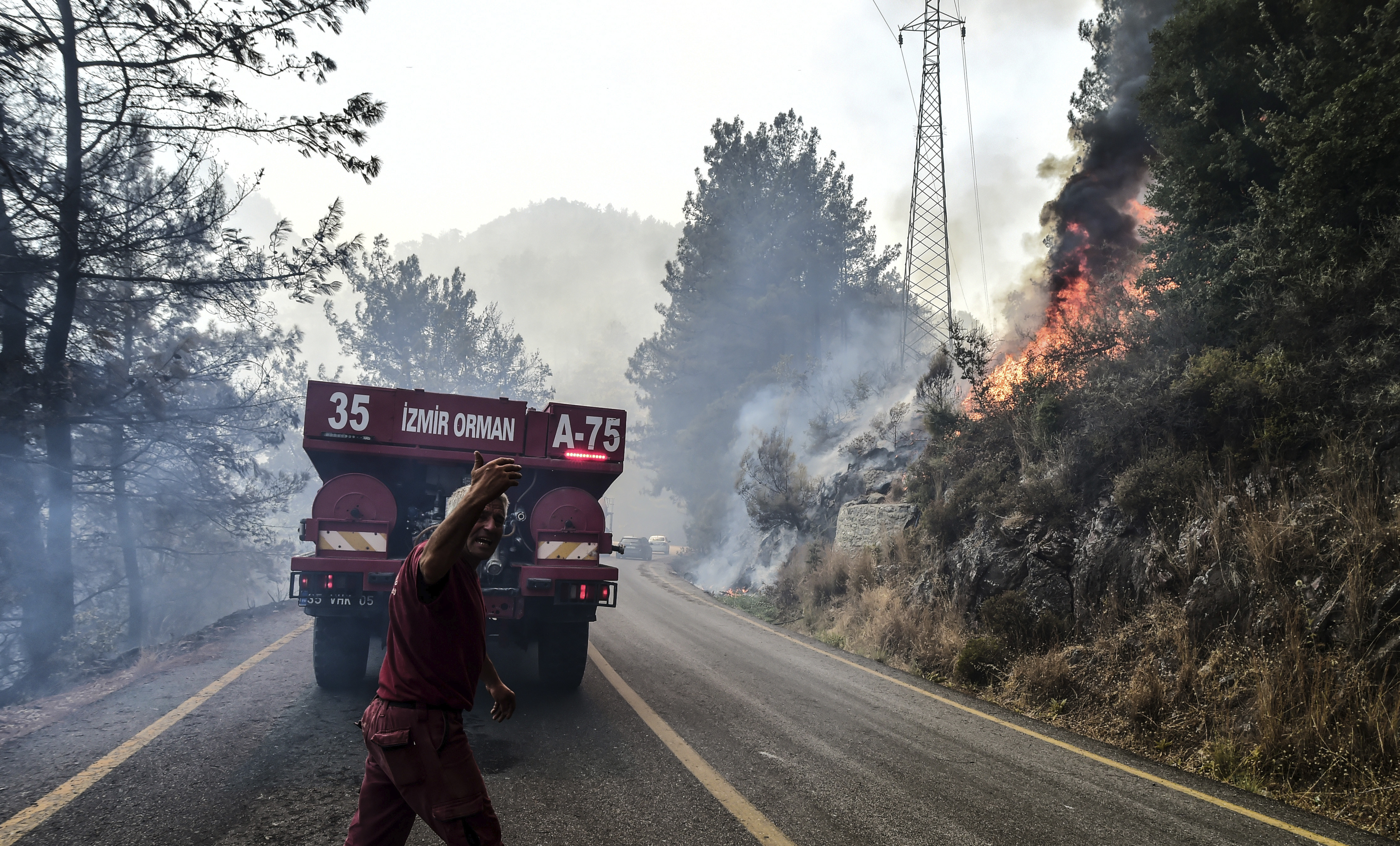 Firefighters work as the wildfires engulf an area near the seashore, forcing people to be evacuated by boats, in Bodrum, Mugla, Turkey, Sunday, Aug. 1, 2021.  (Ismail Coskun/IHA via AP)