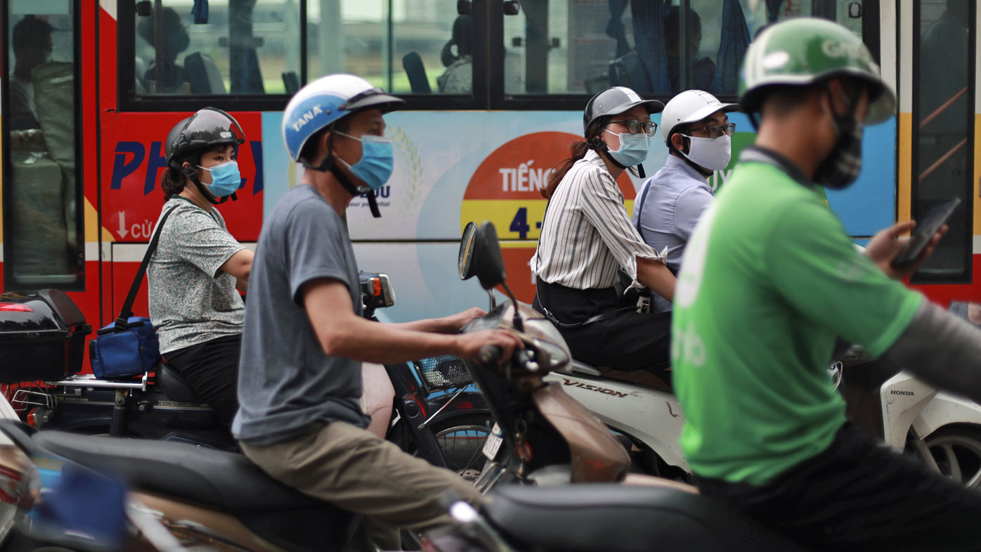 People wear face masks in hopes of curbing the spread of the coronavirus riding mopeds in Hanoi, Vietnam.