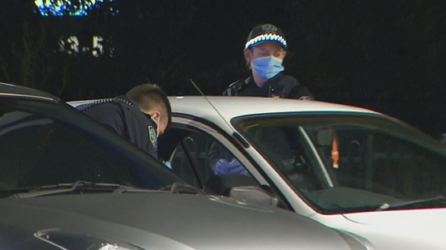 Police examine a car after the stabbing in Adelaide.