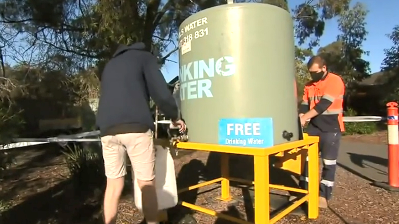 Melbourne residents fill up bottles at a safe water supply.