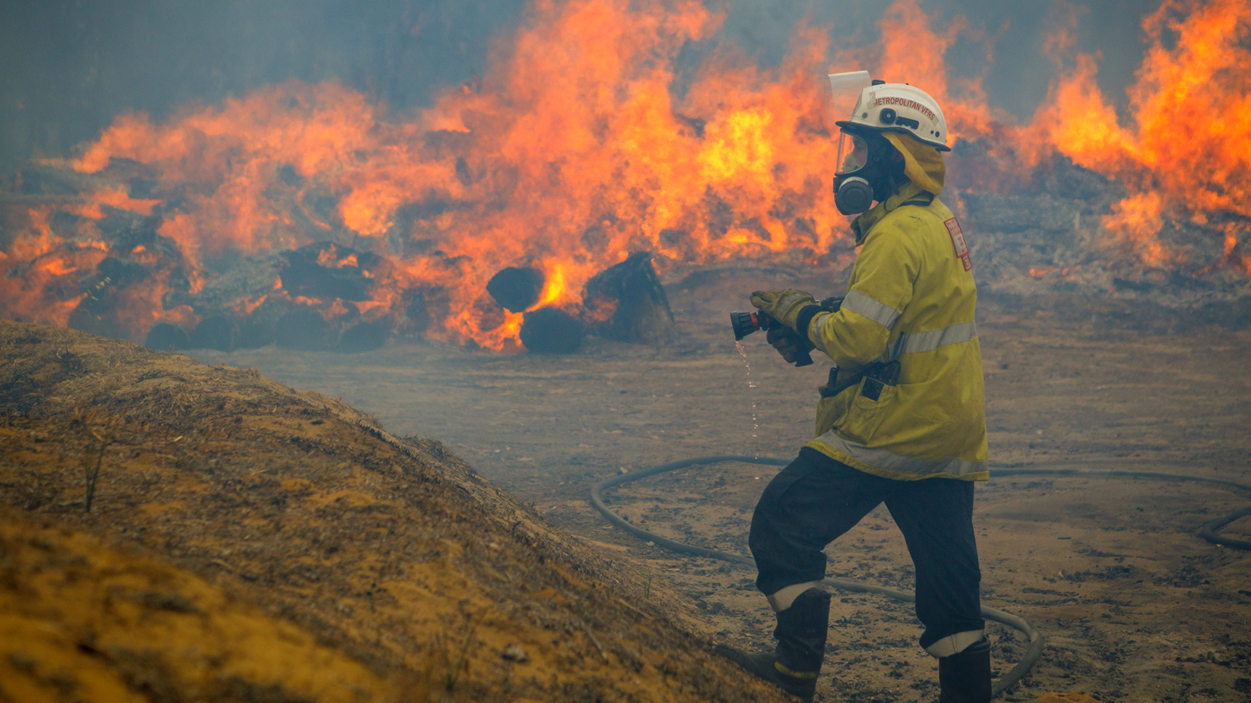 A firefighter stands with a hose as bushfire in Yanchep, Western Australia rages in the background.