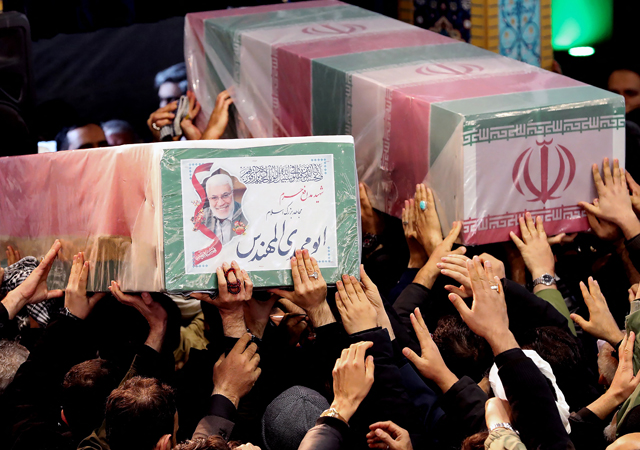 Iranian mourners carrying caskets of slain Iranian military commander Qasem Soleimani (L) and Iraqi paramilitary chief Abu Mahdi al-Muhandis at Tehran University in the Iranian capital