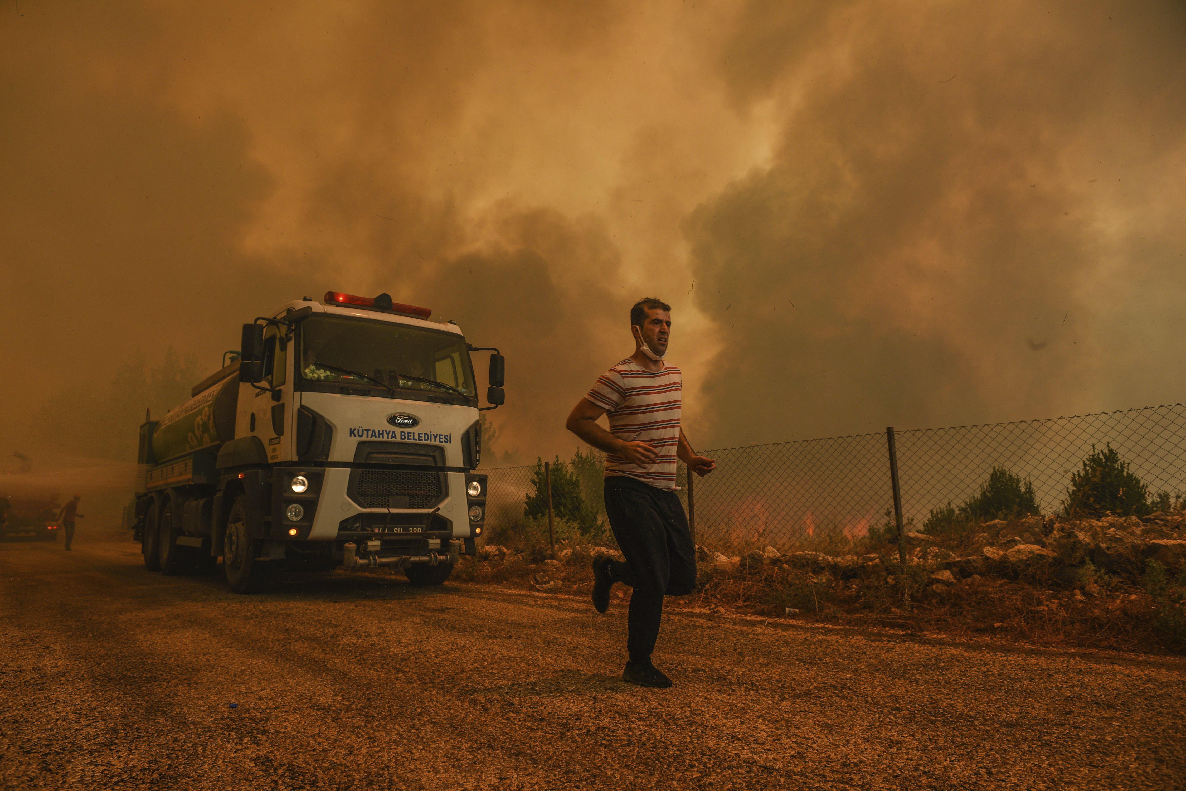 A man runs, in the fire-devastating Sirtkoy village, near Manavgat, Antalya, Turkey, Sunday, Aug. 1, 2021. (AP Photo)