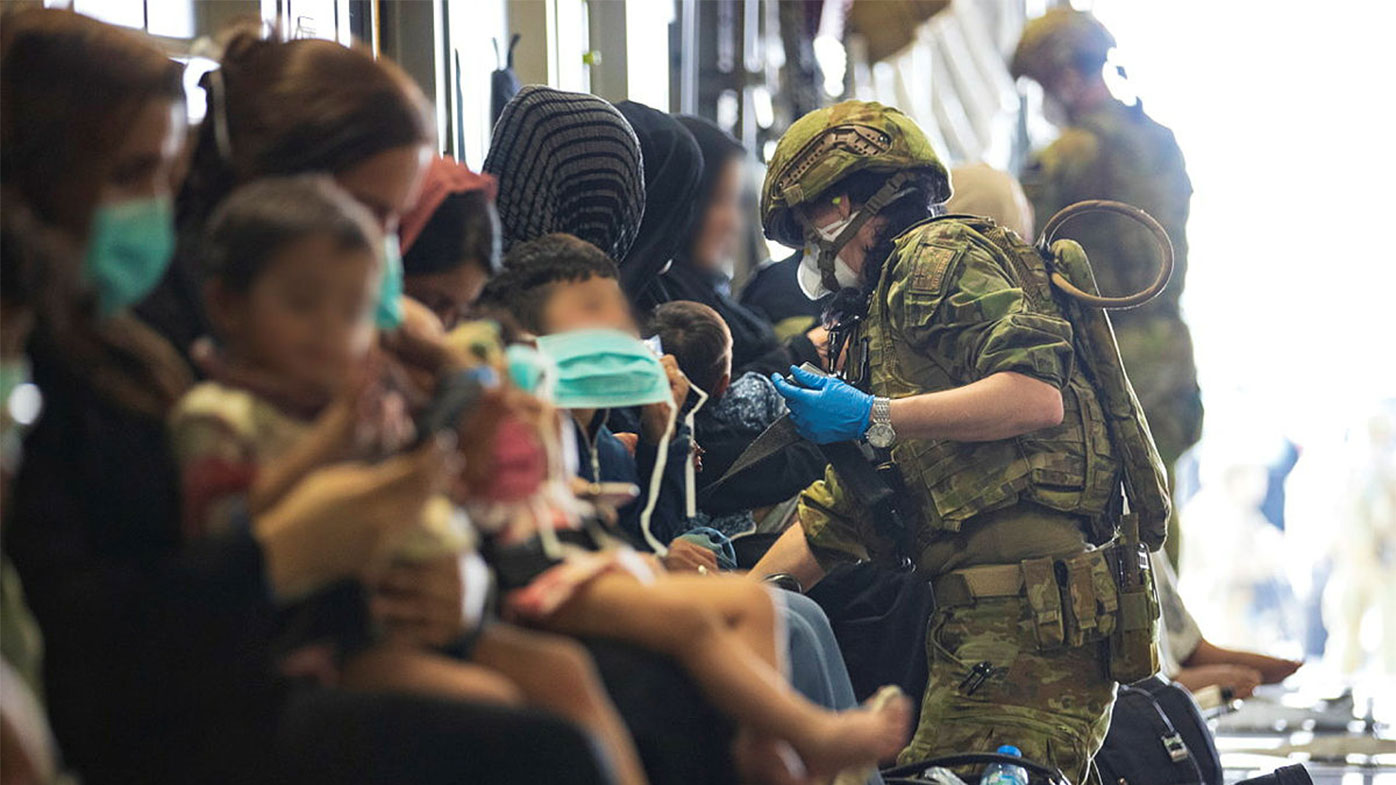 The RAAF Air Load Team assist evacuees into their seats on board the C-17A Globemaster II.