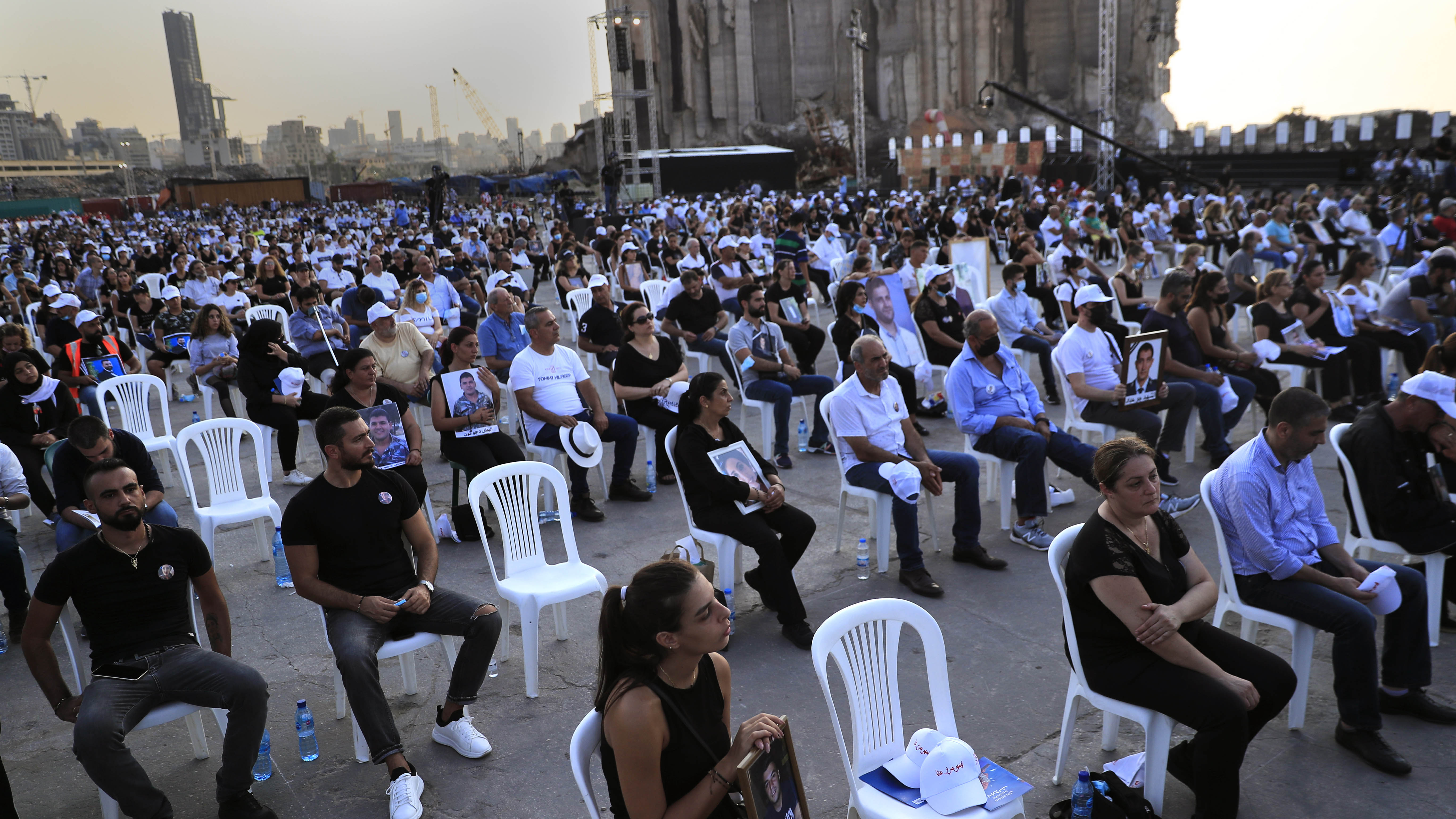 Relatives of victims who were killed in the massive blast last year at the Beirut port holds their portraits as they attend a Mass held to commemorate the first year anniversary of the deadly blast, at the Beirut port, Lebanon.