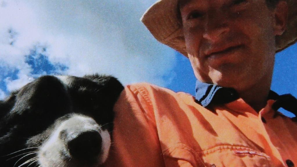 Mathew Dunbar on his property with his dog.