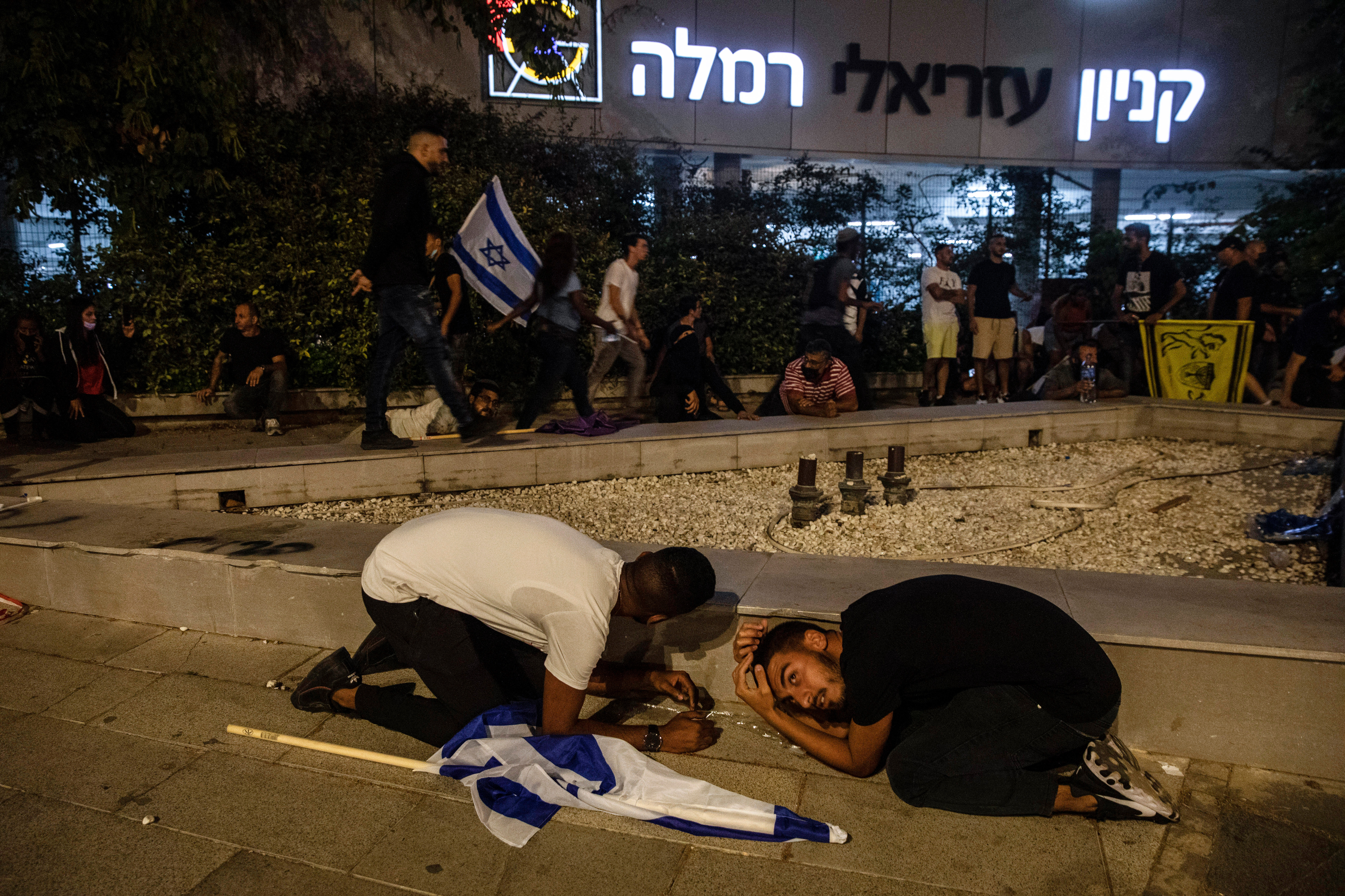 Jewish nationalist demonstrators take cover during a barrage of rockets fired from the Gaza Strip toward central Israel, in the Israeli town of Ramla