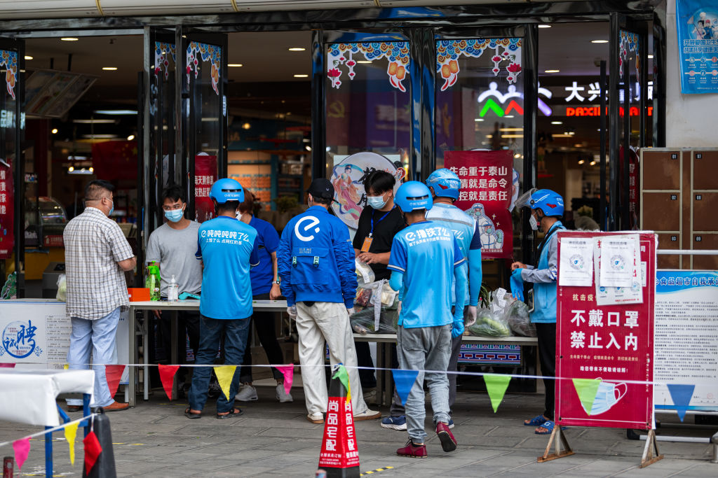 Deliverymen wait for customers' vegetable orders in front of a supermarket amid the COVID-19 epidemic on August 29, 2021 in Ruili, Yunnan Province of China. (Photo by VCG/VCG via Getty Images)