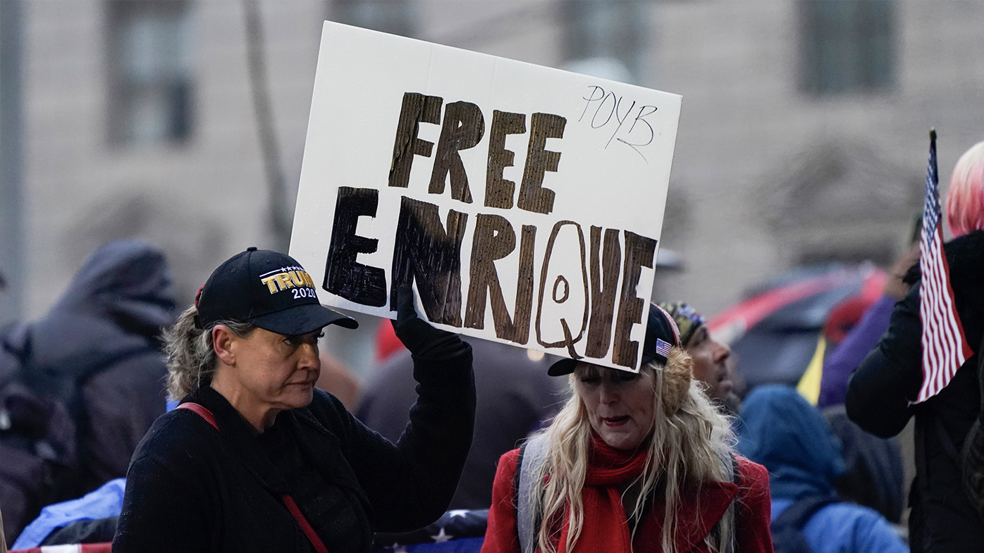 """People hold a sign reading 'Free Enrique' in reference to Proud Boys leader Henry """"Enrique"""" Tarrio, who was arrested on Monday when he arrived back in the District, as they attend a rally at Freedom Plaza Tuesday, Jan. 5, 2021, in Washington, in support of President Donald Trump. Tarrio was arrested and accused of burning a Black Lives Matter banner that was torn down from a historic Black church in downtown Washington last month."""