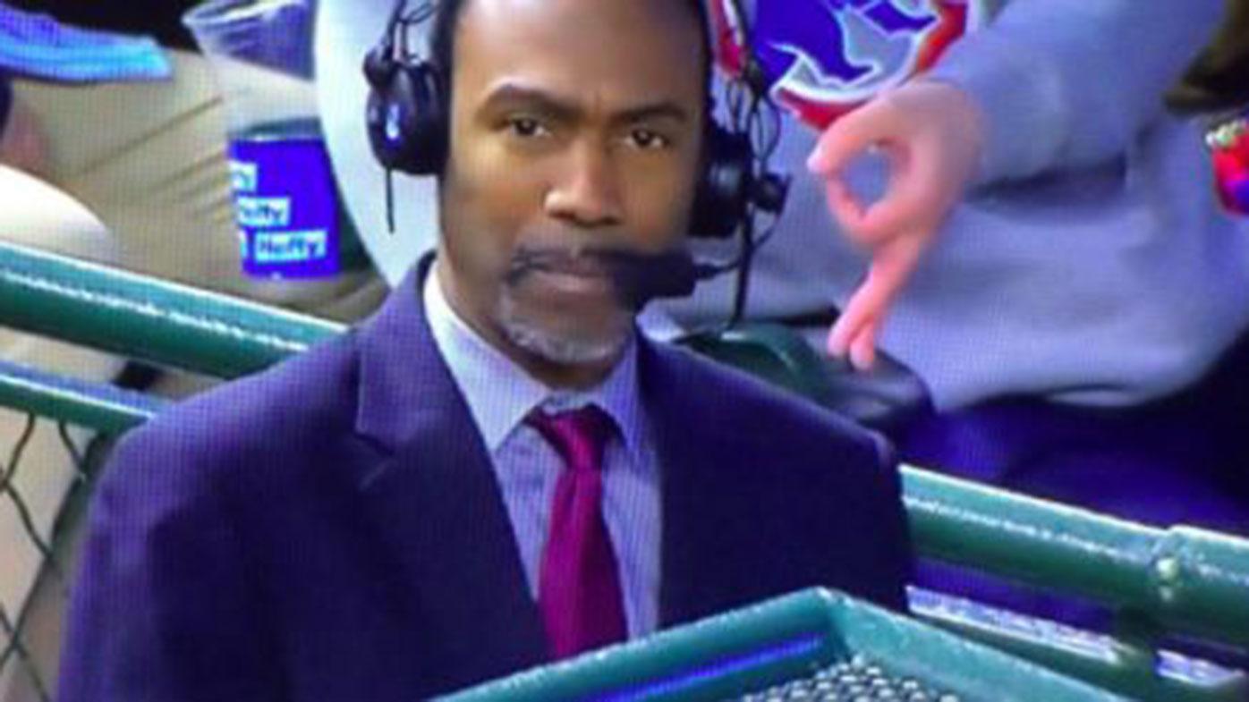 A fan makes a racist gesture behind baseball analyst Doug Glanville.
