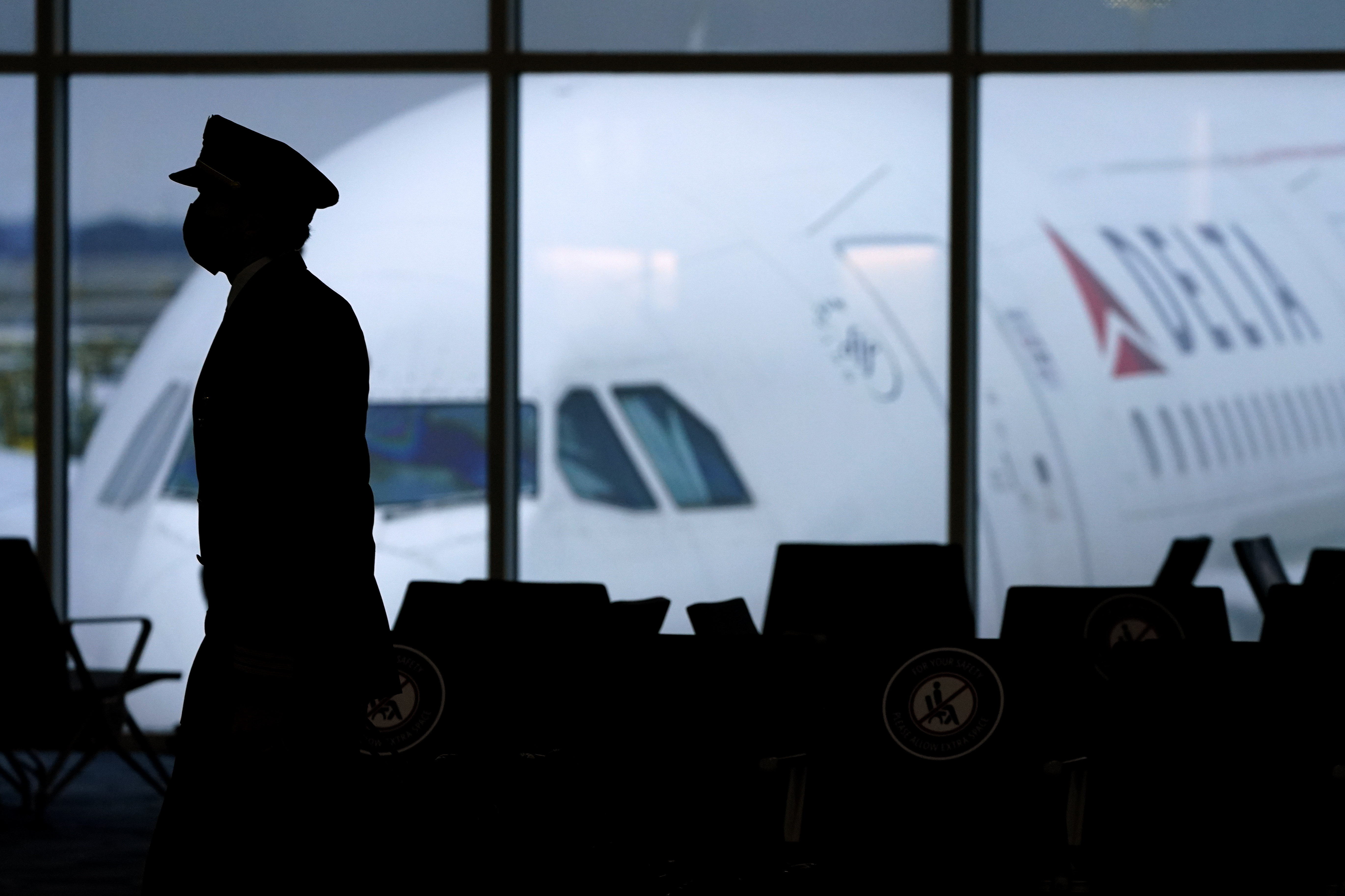 A Delta Airlines pilot wears a face mask to help prevent the spread of the new coronavirus as he walks through a terminal at Hartsfield-Jackson International Airport in Atlanta, Thursday, Feb. 18, 2021. (AP Photo/Charlie Riedel)
