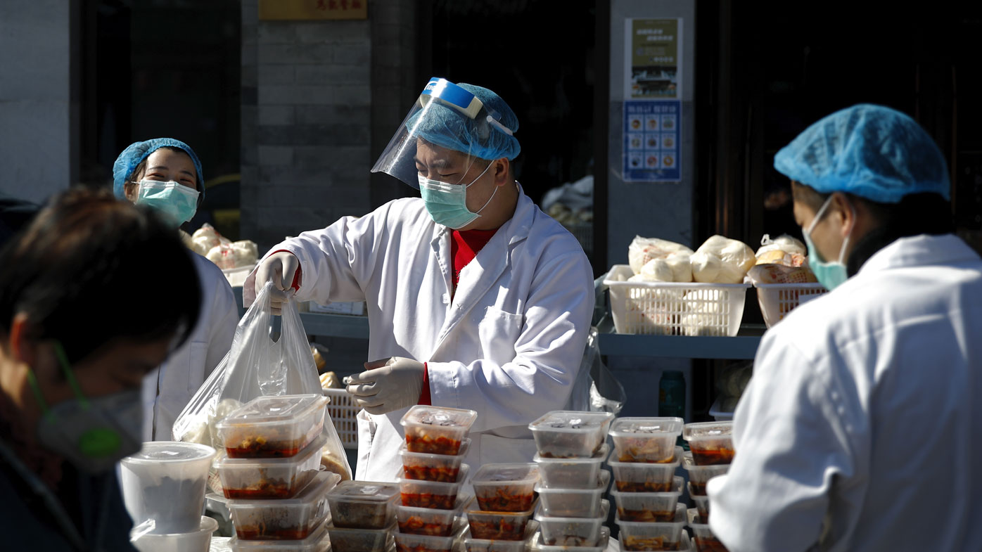 Workers wearing protective face masks pack food orders for customers outside a restaurant only offering take-out business to prevent people gathering following the coronavirus outbreak in Beijing.