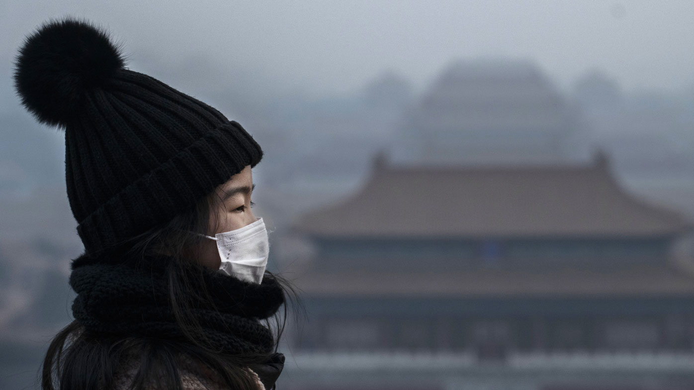 A Chinese girl wears a protective mask as she stands on an overlook towards the Forbidden City, which was closed by authorities, during the Chinese New Year holiday on January 26, 2020 in Beijing, China.