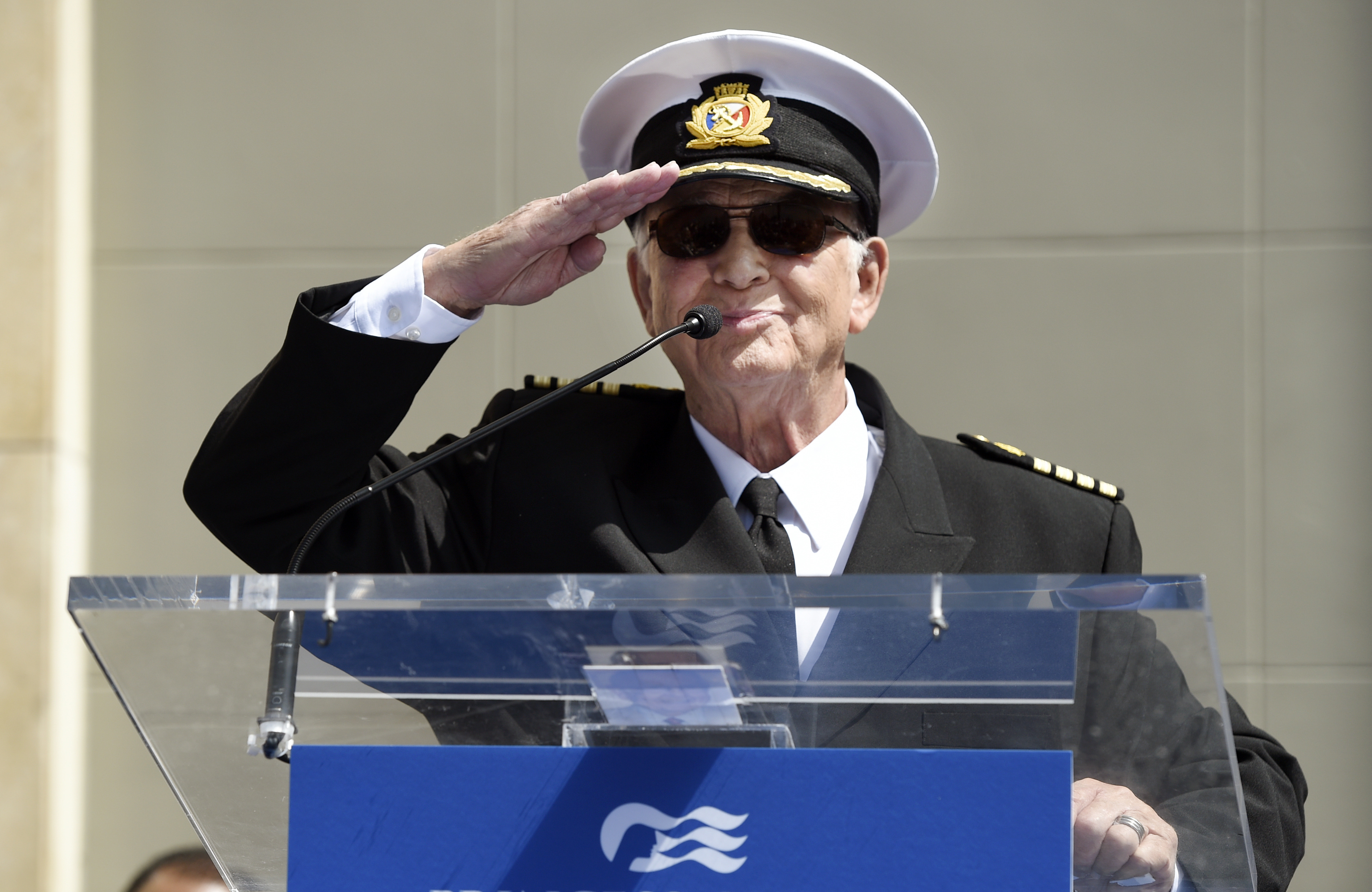 """Gavin MacLeod, an original cast member in the television series """"The Love Boat,"""" salutes the crowd as he speaks at a Friends of Hollywood Walk of Fame honorary star plaque ceremony for the cast and Princess Cruises."""