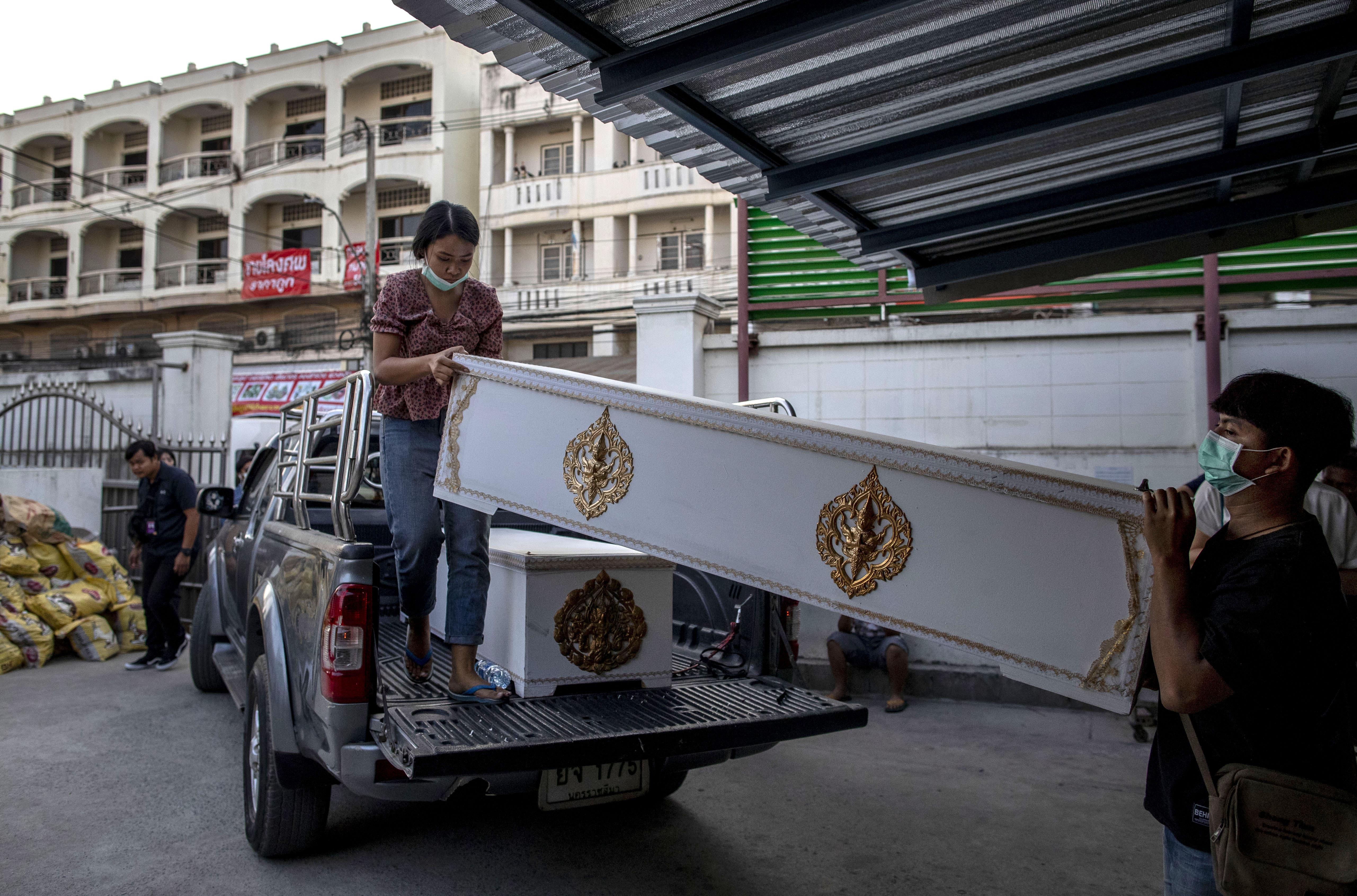 Morgue staff carry in coffins in Korat, Nakhon Ratchasima, Thailand