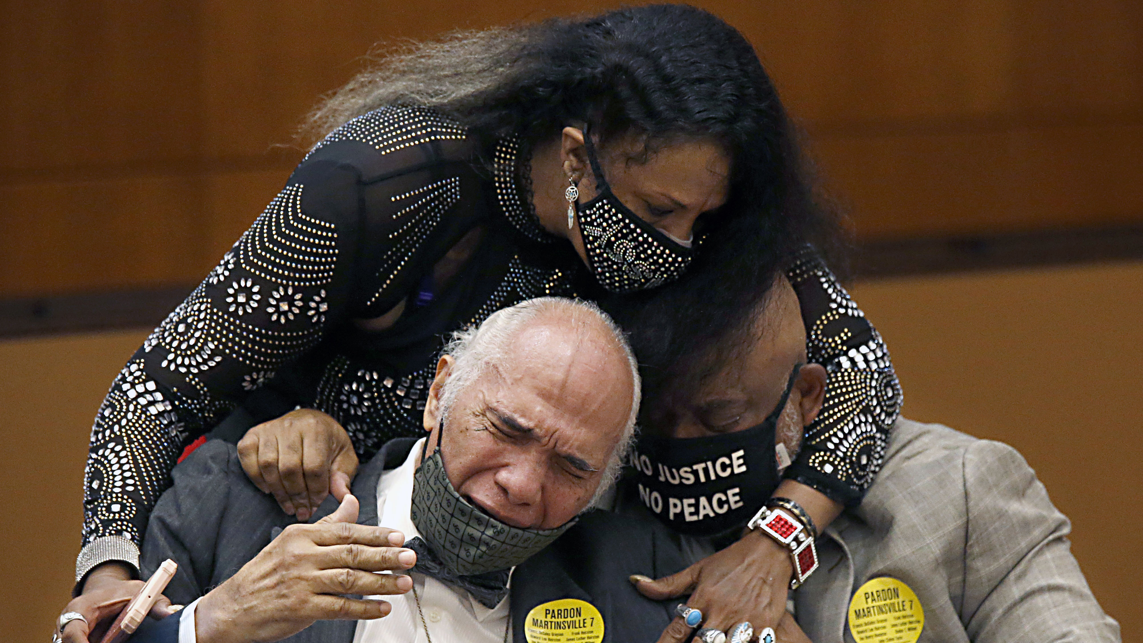 Rose Grayson, niece of Francis DeSales Grayson, top, comforts James Grayson, son of Francis DeSales Grayson, left, and Rudy MCollum, great nephew of Francis DeSales Grayson, one of the Martinsville Seven after posthumous pardons issued.