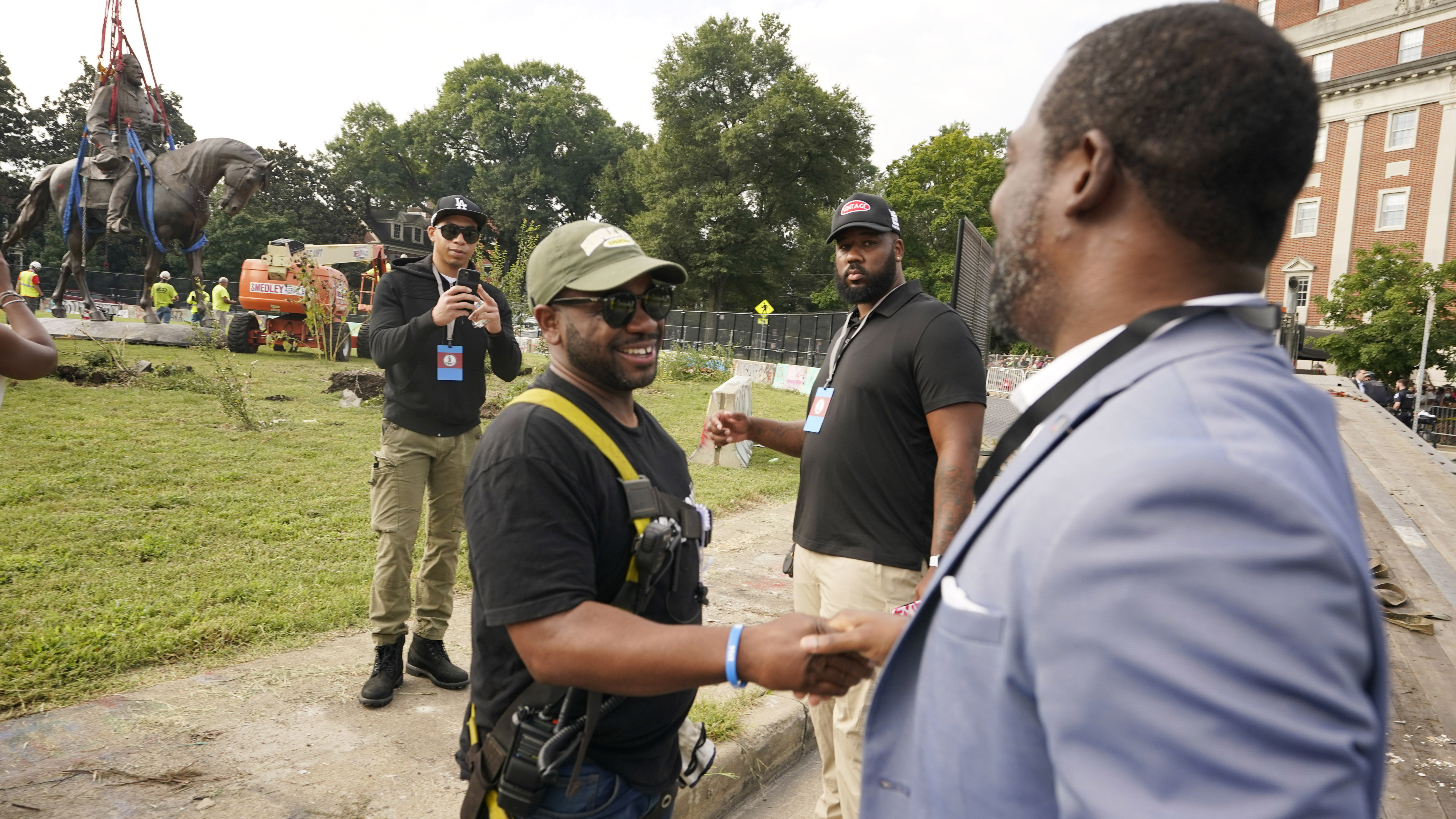 Devon Henry, left, was the owner of the construction company that removed the statue shook hands with Richmond Mayor, Levar Stoney, right.