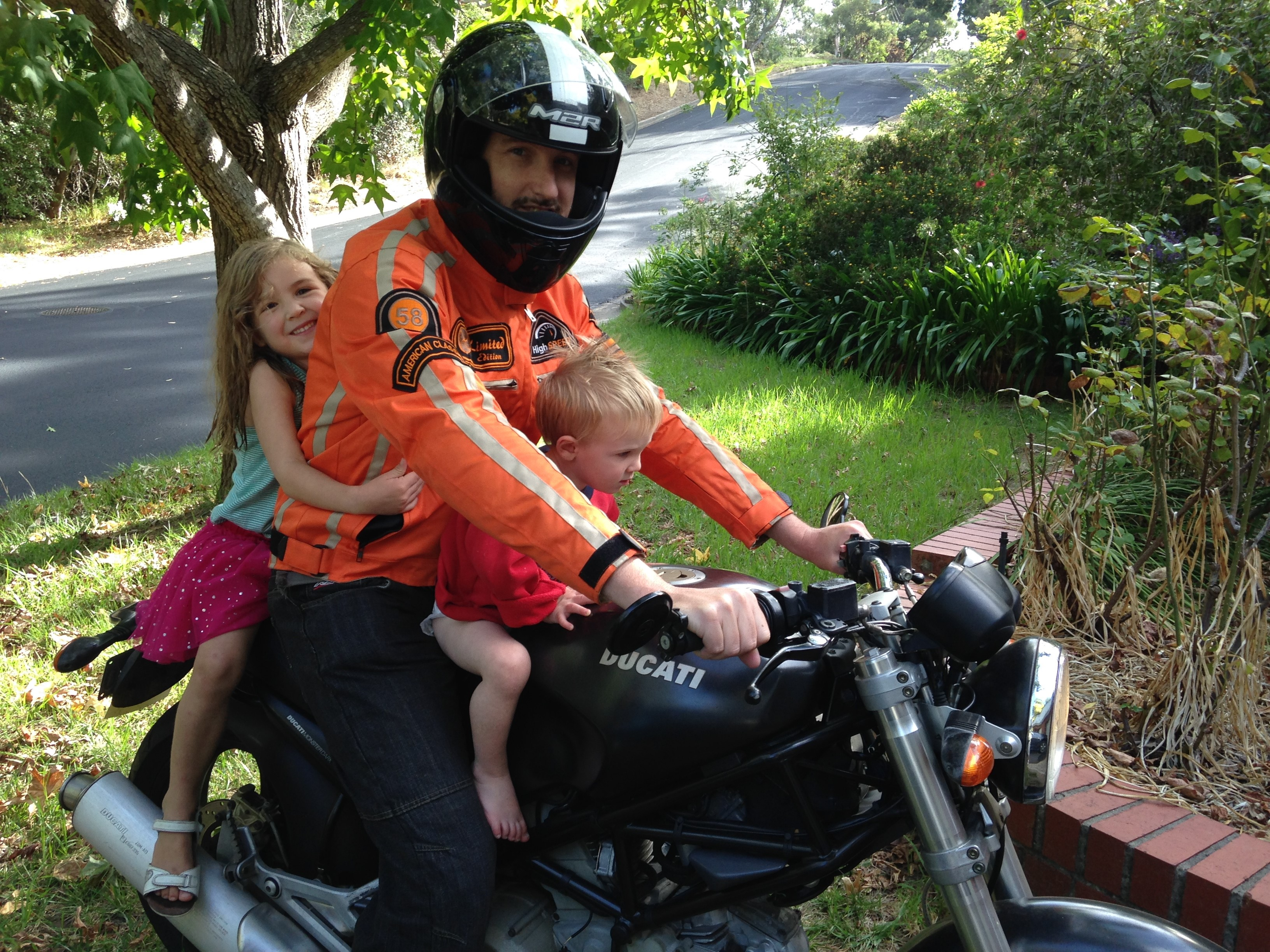 Leigh on his motorbike with his children, Zoe and Finn.