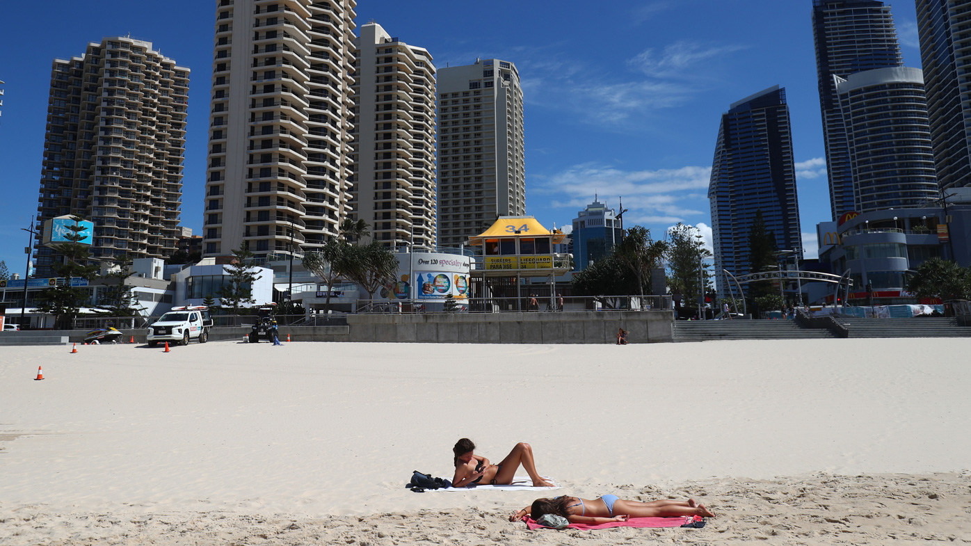 People lie on the beach at Surfers Paradise beach in Gold Coast, Australia.