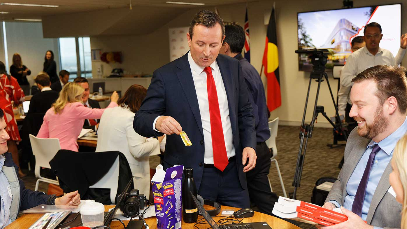 WA Premier Mark McGowan looks thrilled after reaching into a box of Favourites and getting a Flake during the budget lockup yesterday.
