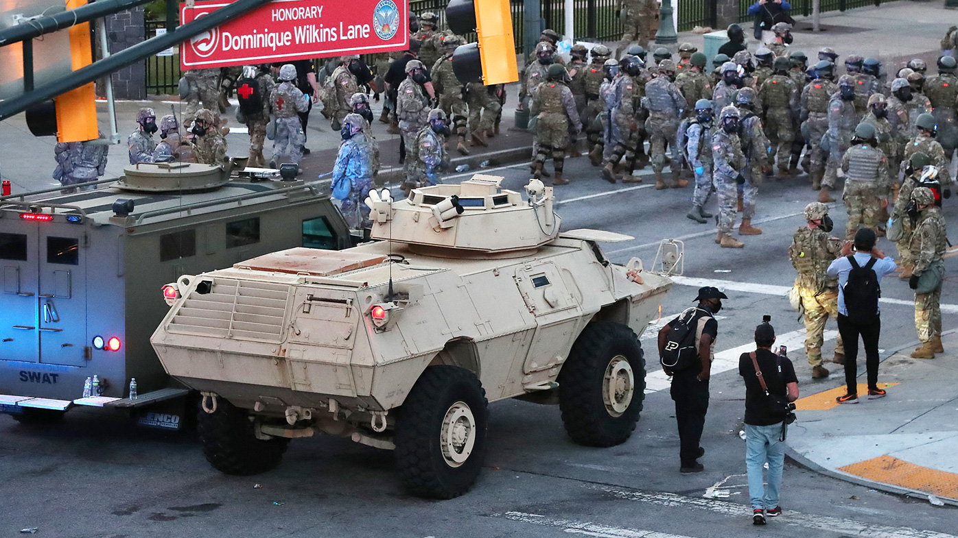 The Georgia Army National Guard mans an armoured security vehicle following troops down Centennial Olympic Park Drive/Honorary Dominique Wilkins Lane to push back and disperse protesters after curfew
