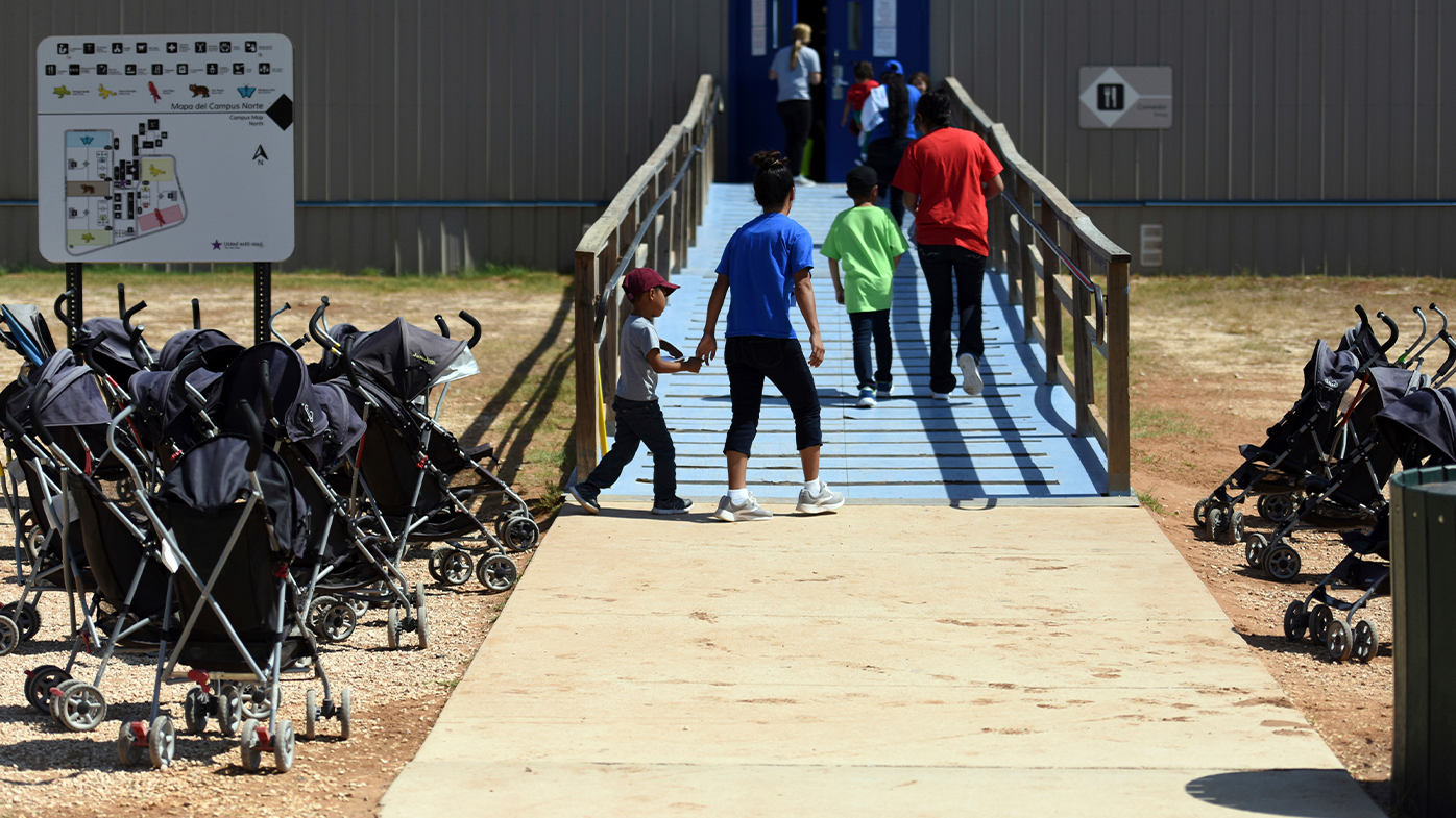FILE -In this Aug. 9, 2018, file photo, provided by U.S. Immigration and Customs Enforcement, immigrants walk into a building at South Texas Family Residential Center in Dilley, Texas.
