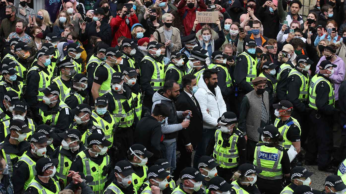 Two men stand surrounded by police and protesters, after being released from an Immigration Enforcement police van.