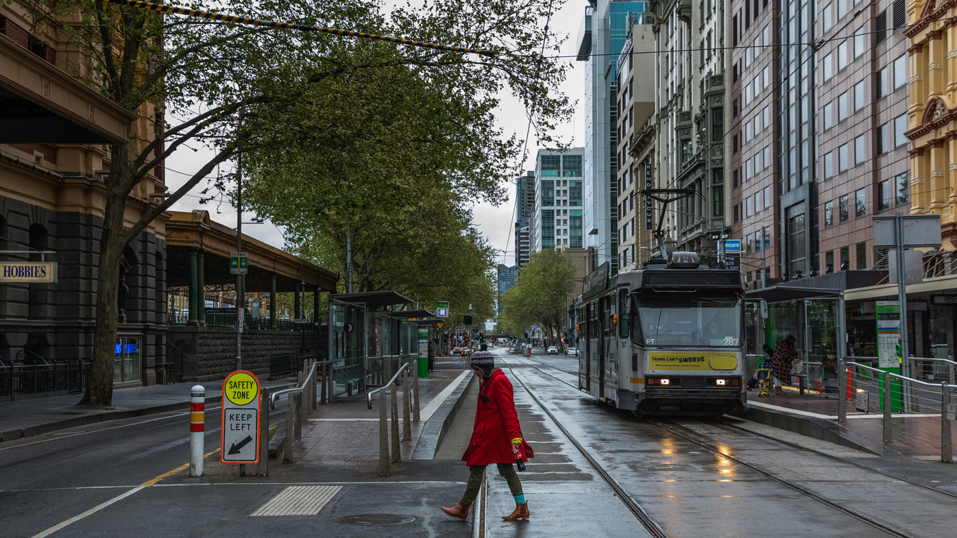 A lone woman is seen crossing the usually busy Flinders Street Elizabeth Street intersection on September 25, 2020 in Melbourne, Australia.